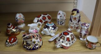 Ten Royal Crown Derby paperweights, a miniature Derby cup and a cream jug