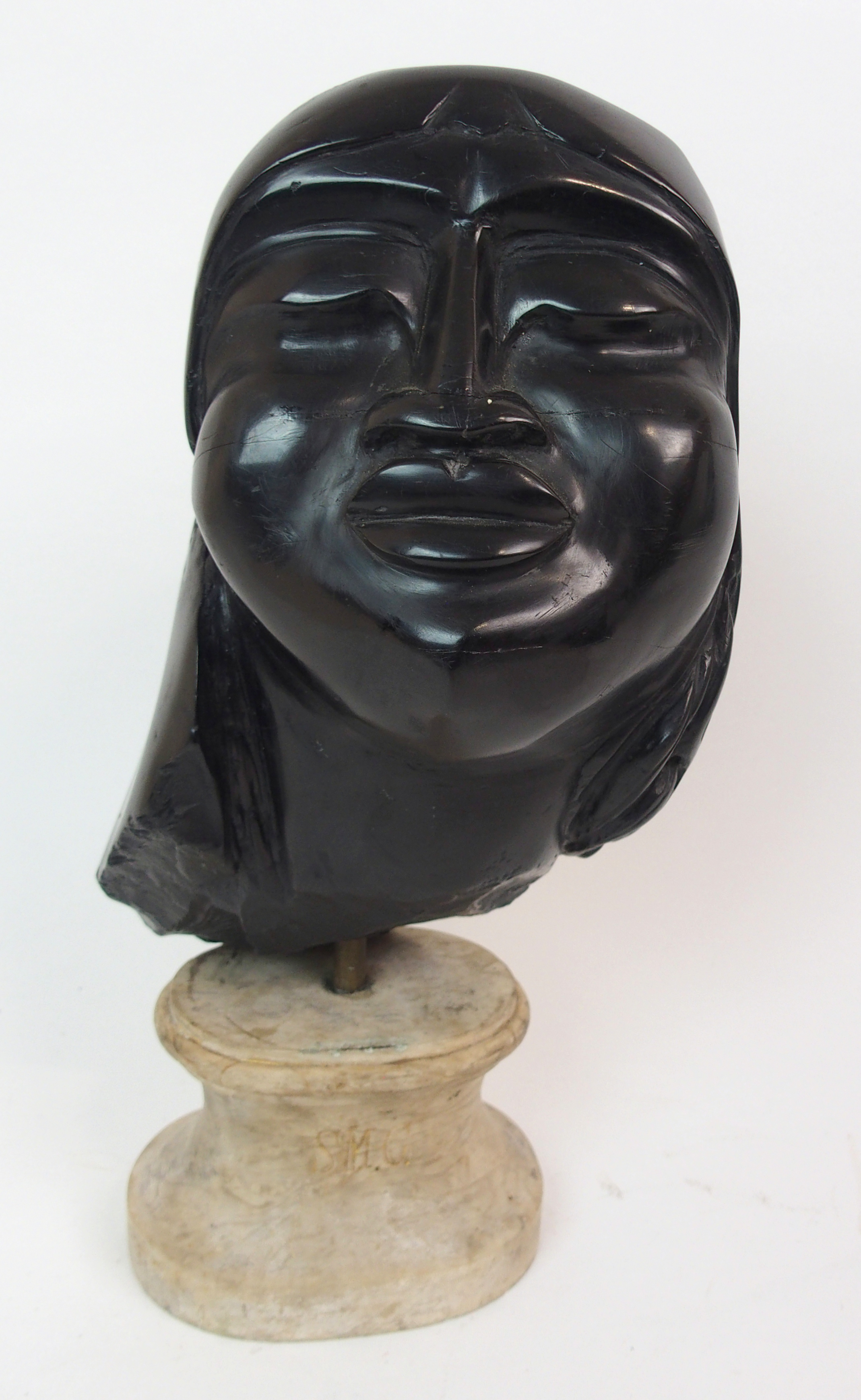Lot 57 - A COAL CARVED HEAD OF A WOMAN wearing headband and with a marble socle engraved SMC, the head 20cm