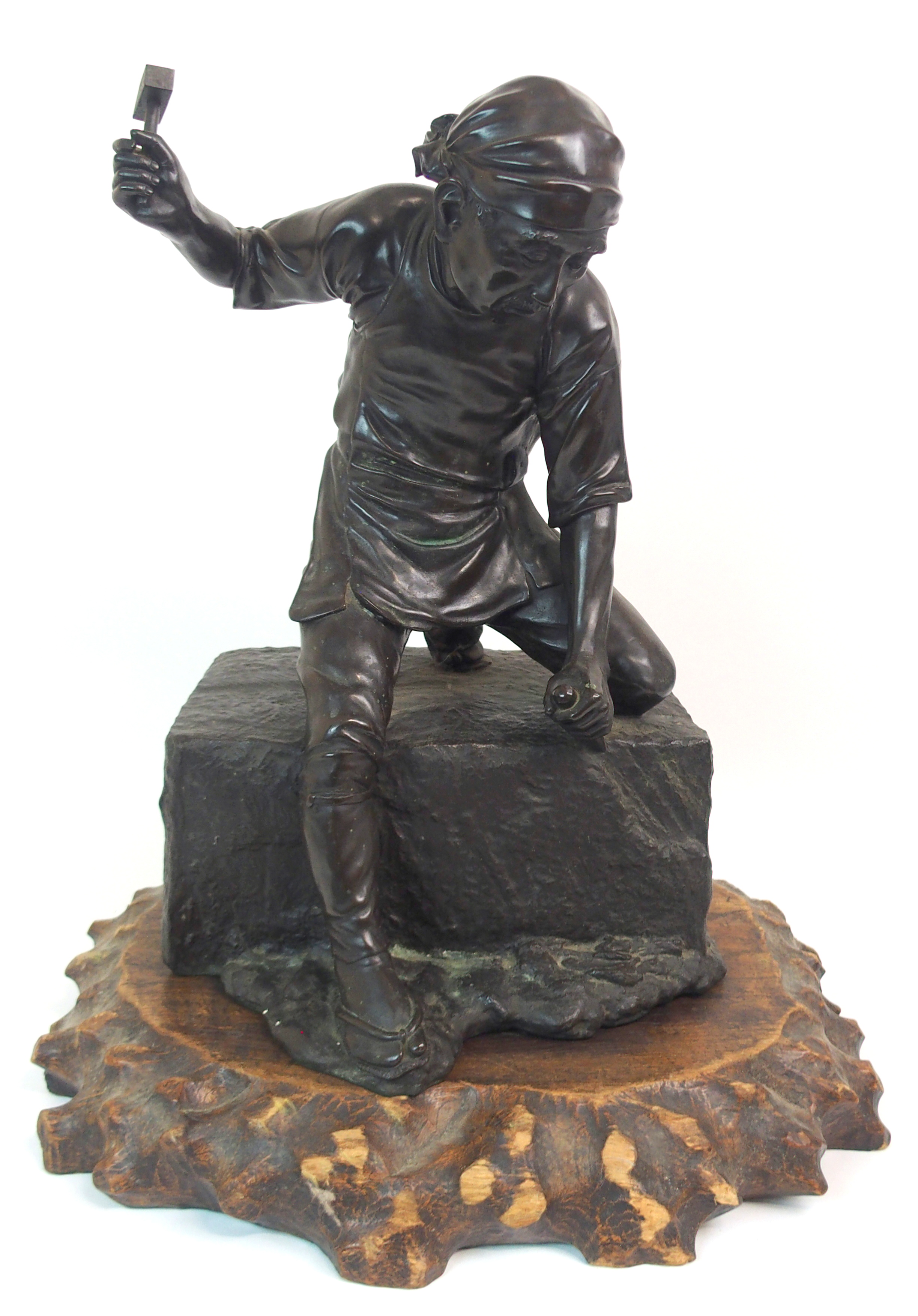 Lot 28 - A JAPANESE BRONZE OF A STONE MASON standing over a large stone block with hammer and chisel,