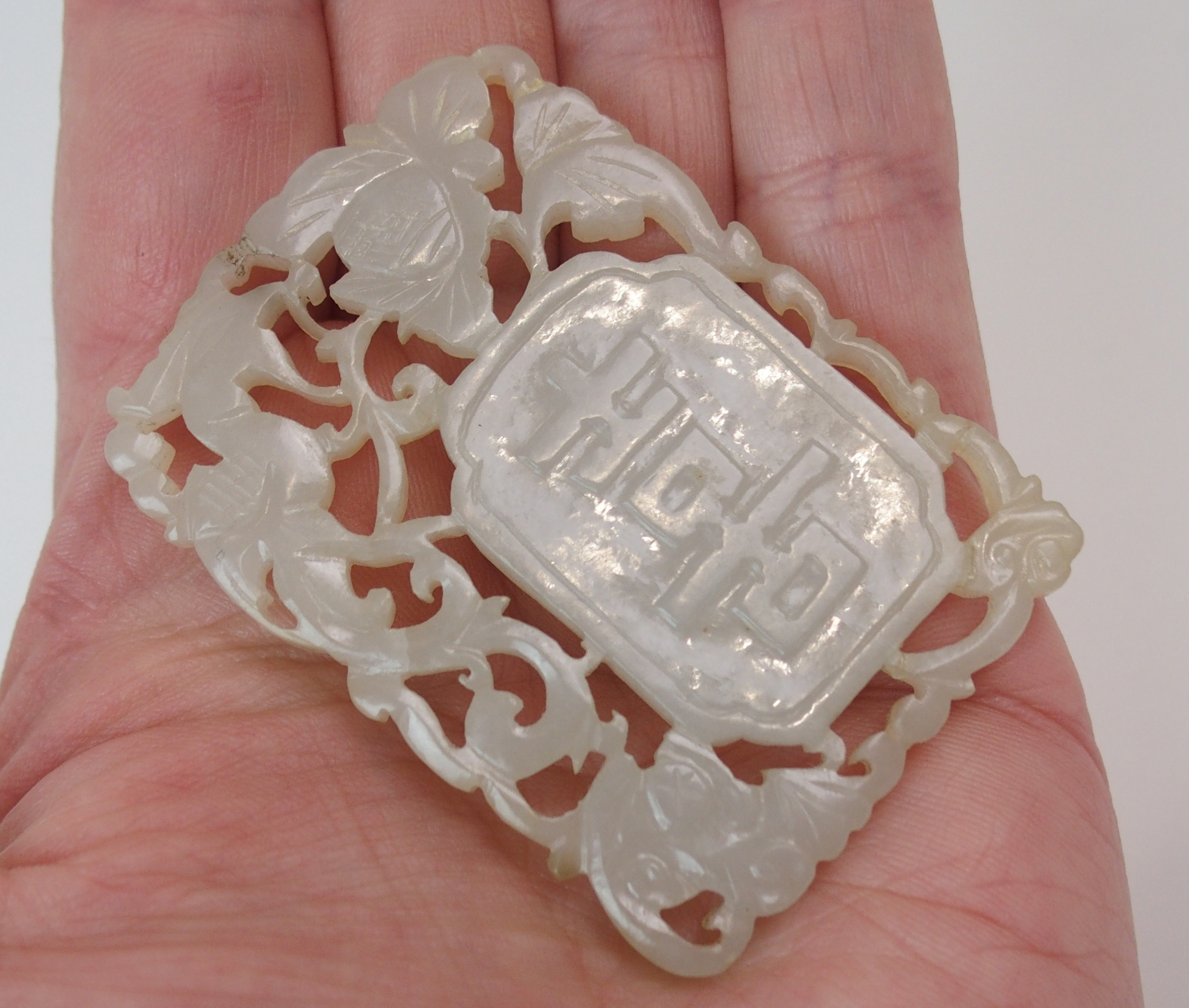Lot 38 - A CHINESE JADE PENDANT carved with shou characters surrounded by a bird and foliage, 5.8cm x 4cm