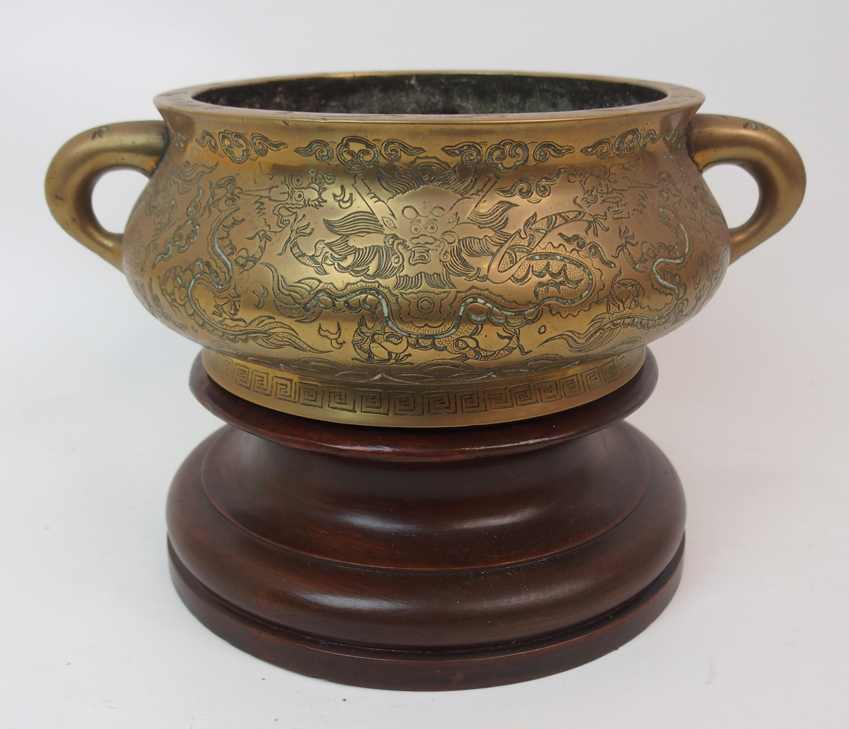 Lot 60 - A CHINESE BRASS TWO-HANDLED CENSER engraved allover with dragons, waves and clouds above a key-