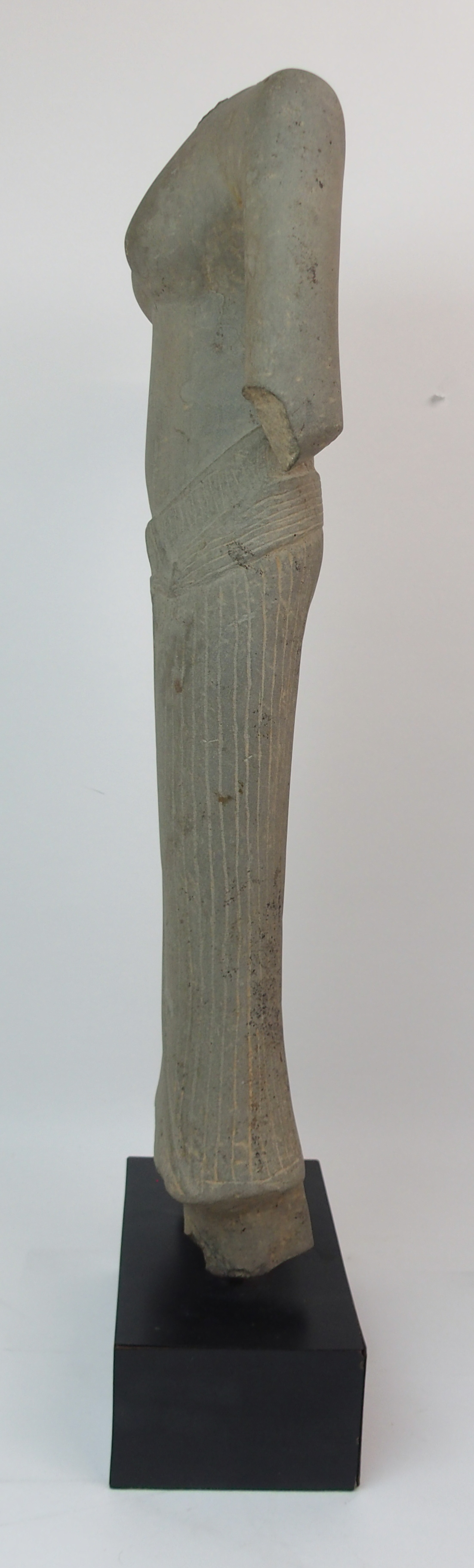 Lot 45 - AN ASIAN STONE CARVING OF A FEMALE TORSO bare chested and wearing a ribbon tied patterned dress, (
