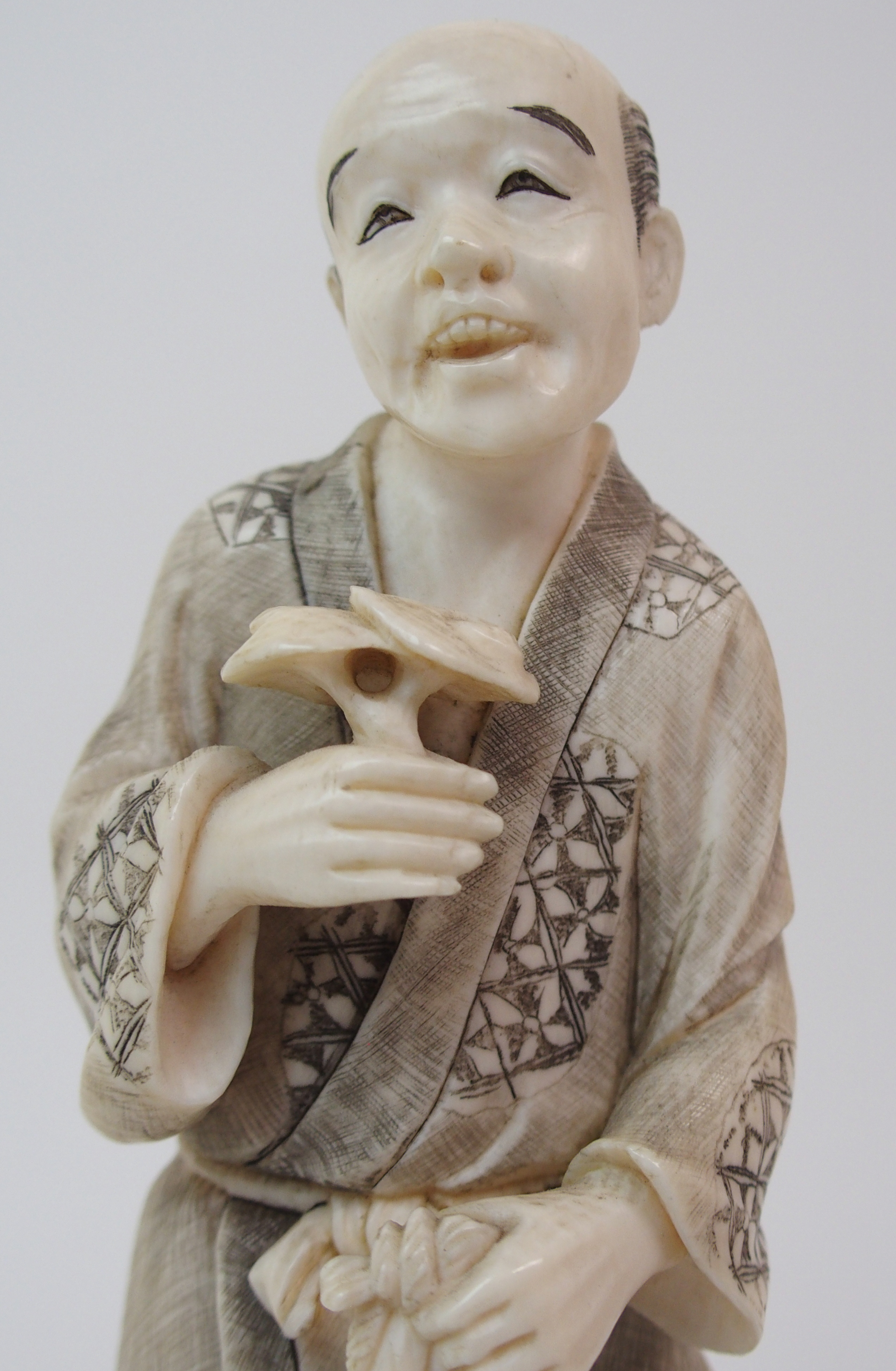 Lot 21 - AN IVORY OKIMONO OF A HUNTSMAN with game, shotgun and dog, 17cm high and a fruit gatherer holding