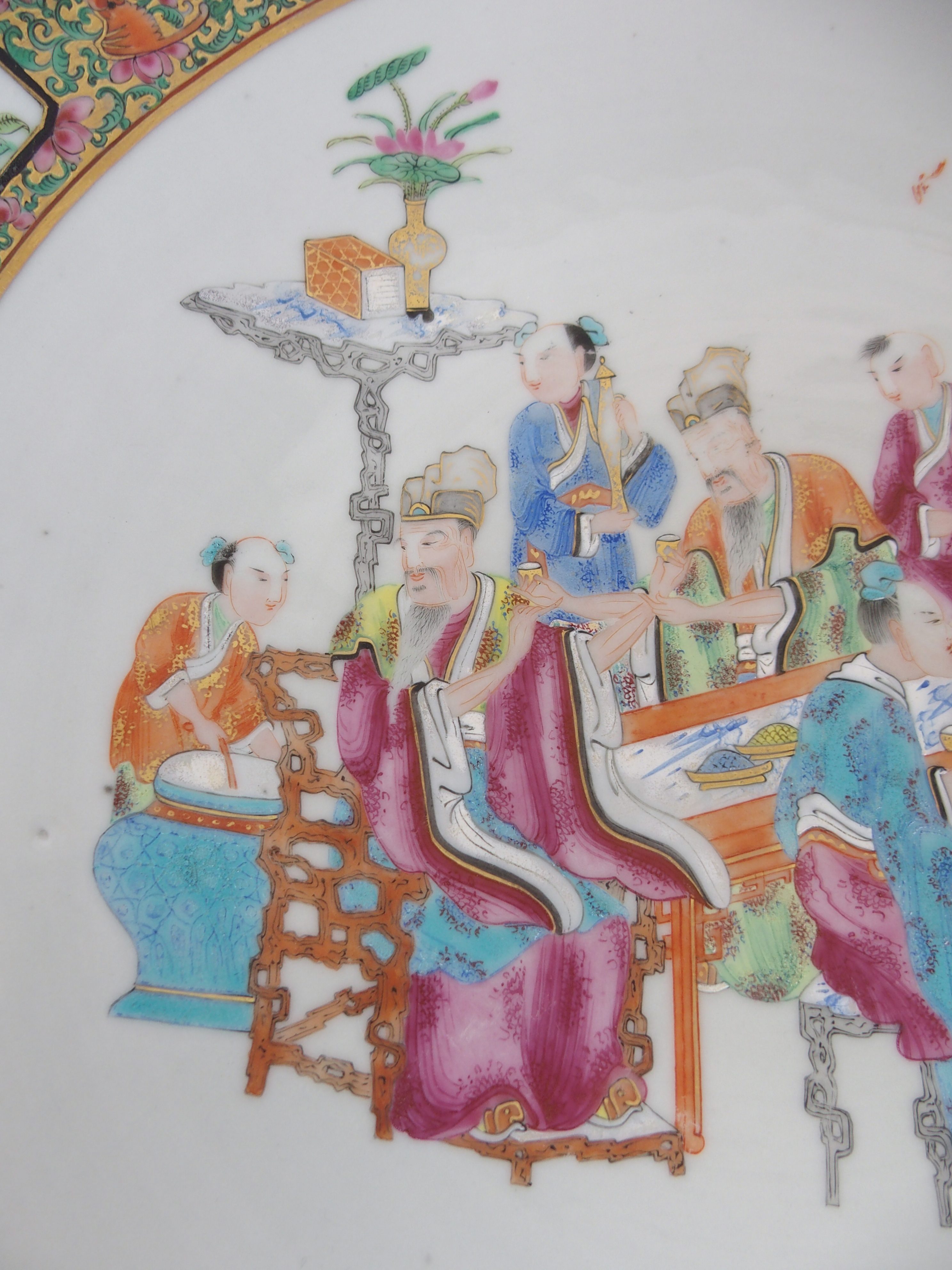 Lot 4 - A CANTON CHARGER painted with scholars and attendants at a table within a dense gilt and