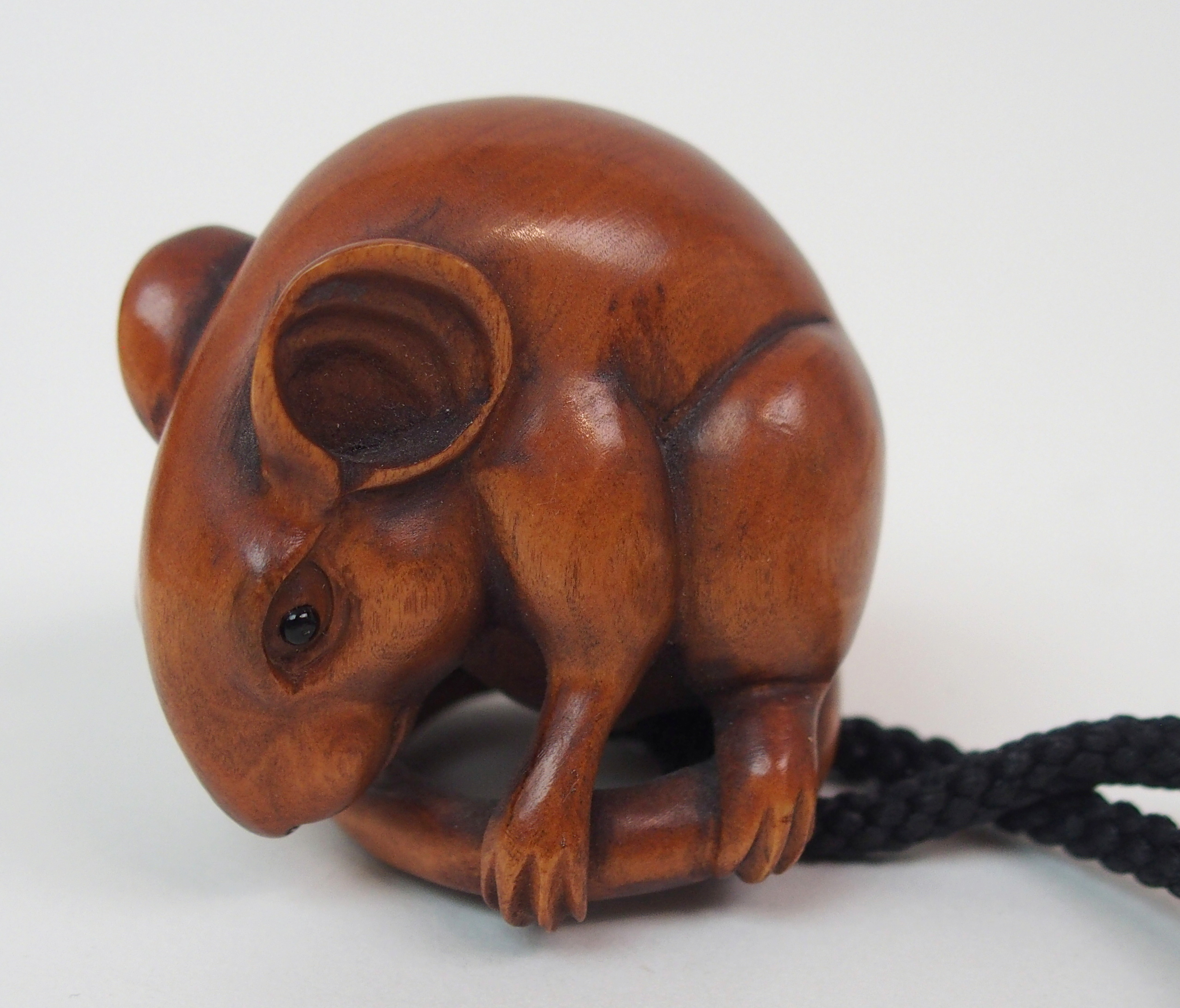 Lot 18 - A JAPANESE CARVED WOOD NETSUKE OF A RAT seated holding its tail, signed, 3.5cm high, with Komai