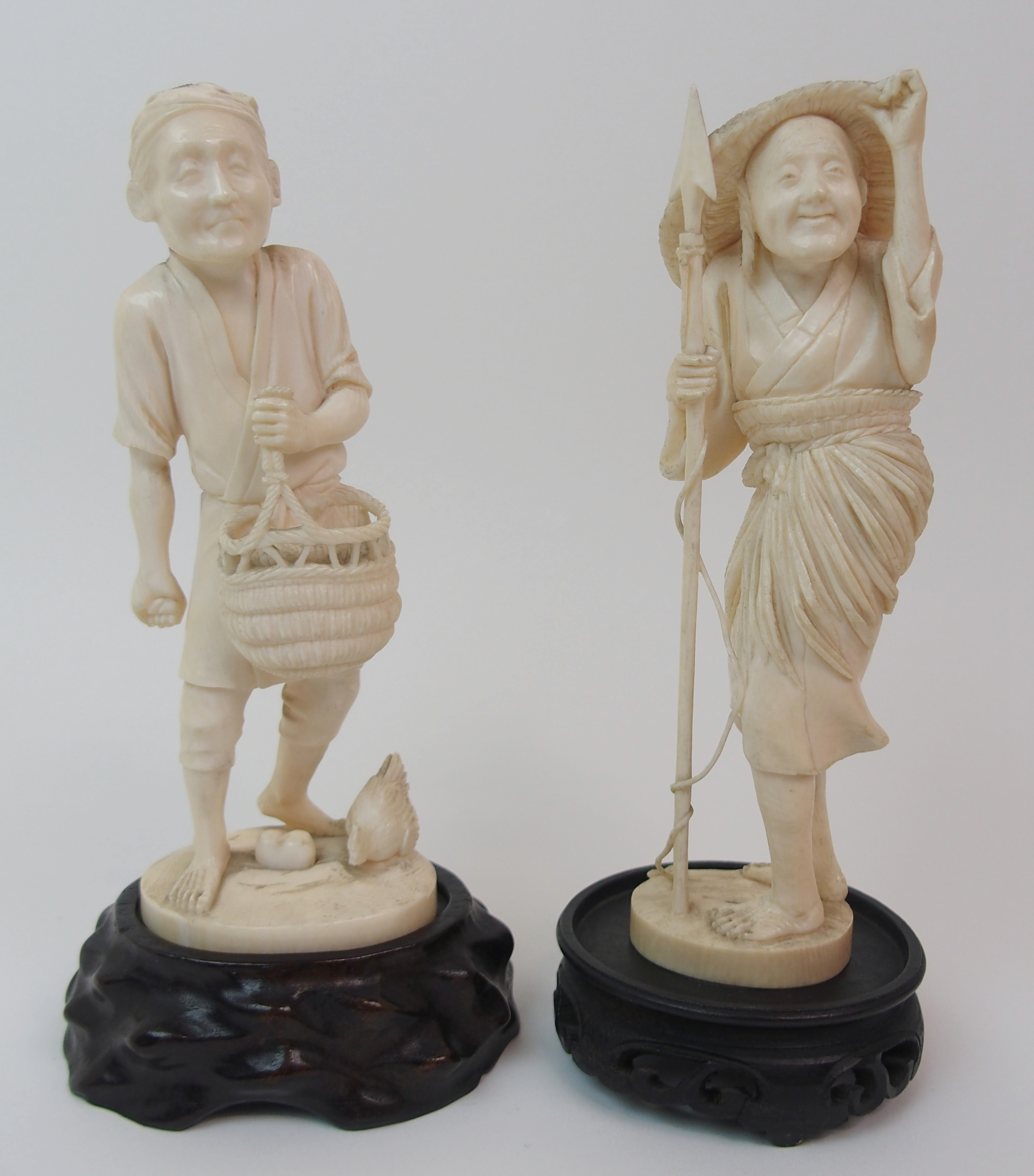 Lot 22 - AN IVORY OKIMONO OF A FISHERWOMAN holding a harpoon, 17cm high and a farmer feeding chickens, 16.5cm