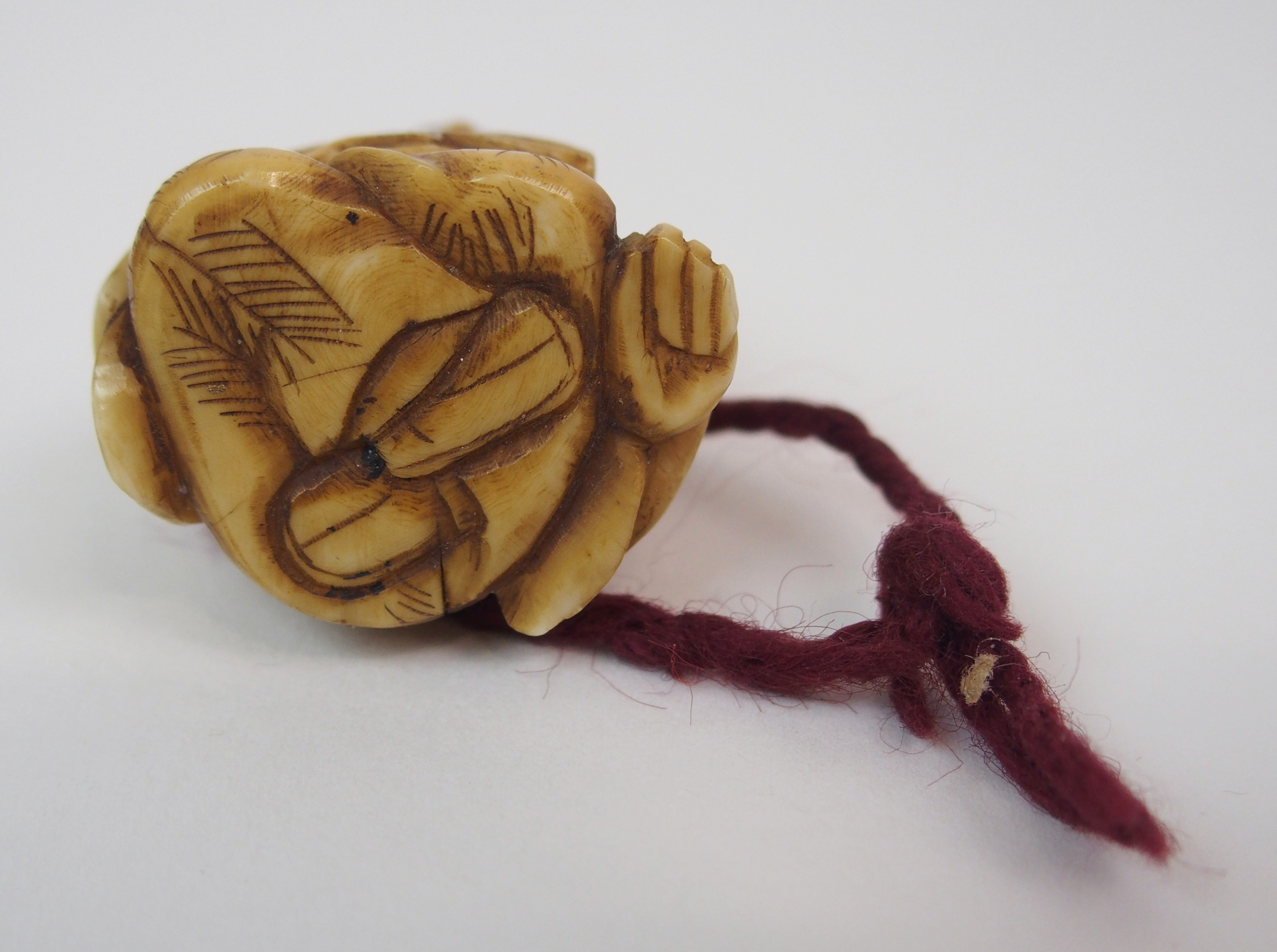Lot 32 - AN AFRICAN HARDWOOD KNOBKERRIE rootwood club with geometric carved grip, 41cm long, an ivory netsuke