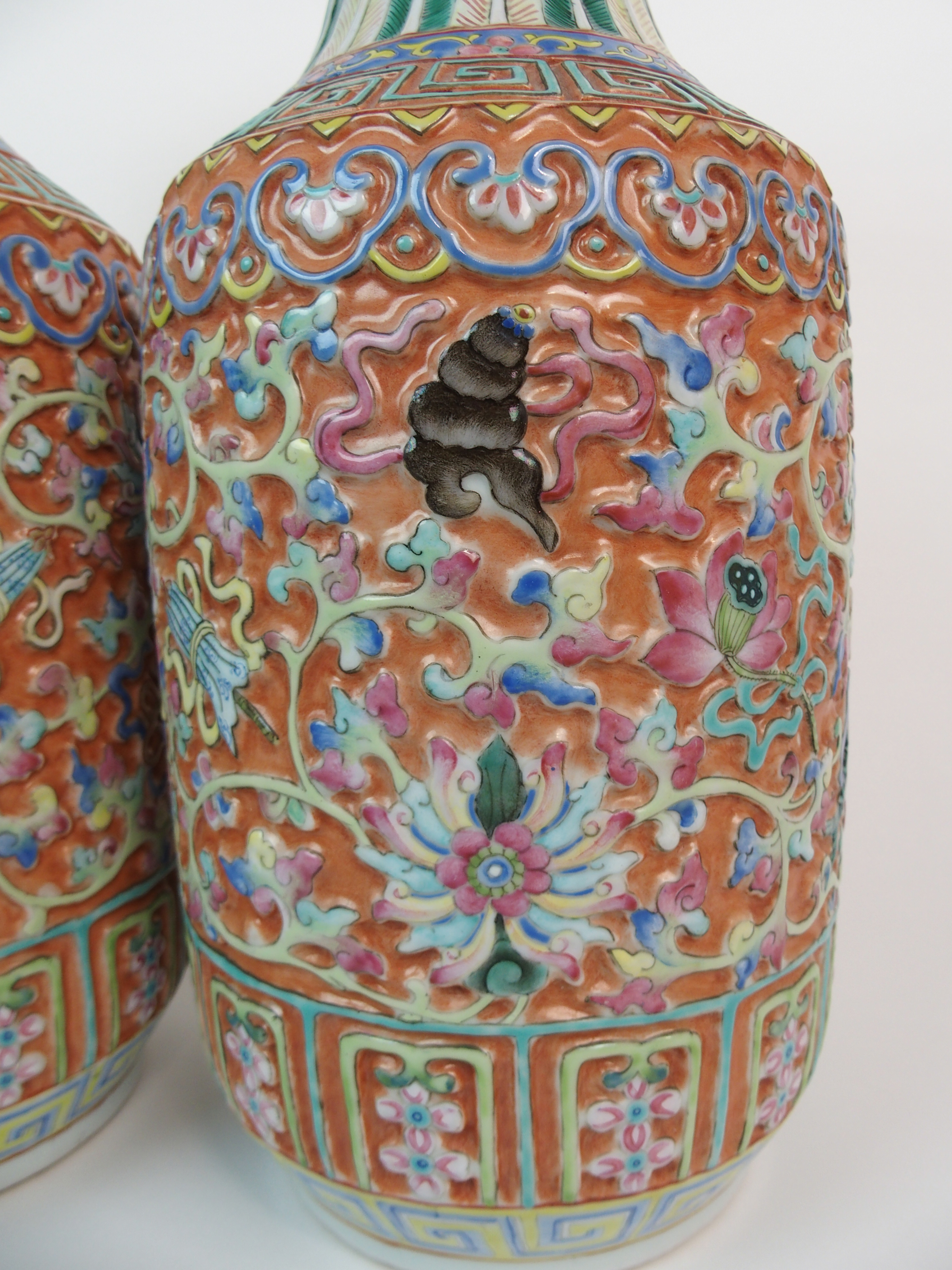 Lot 29 - A PAIR OF CANTON RELIEF MOULDED BALUSTER VASES decorated with precious symbols within key pattern