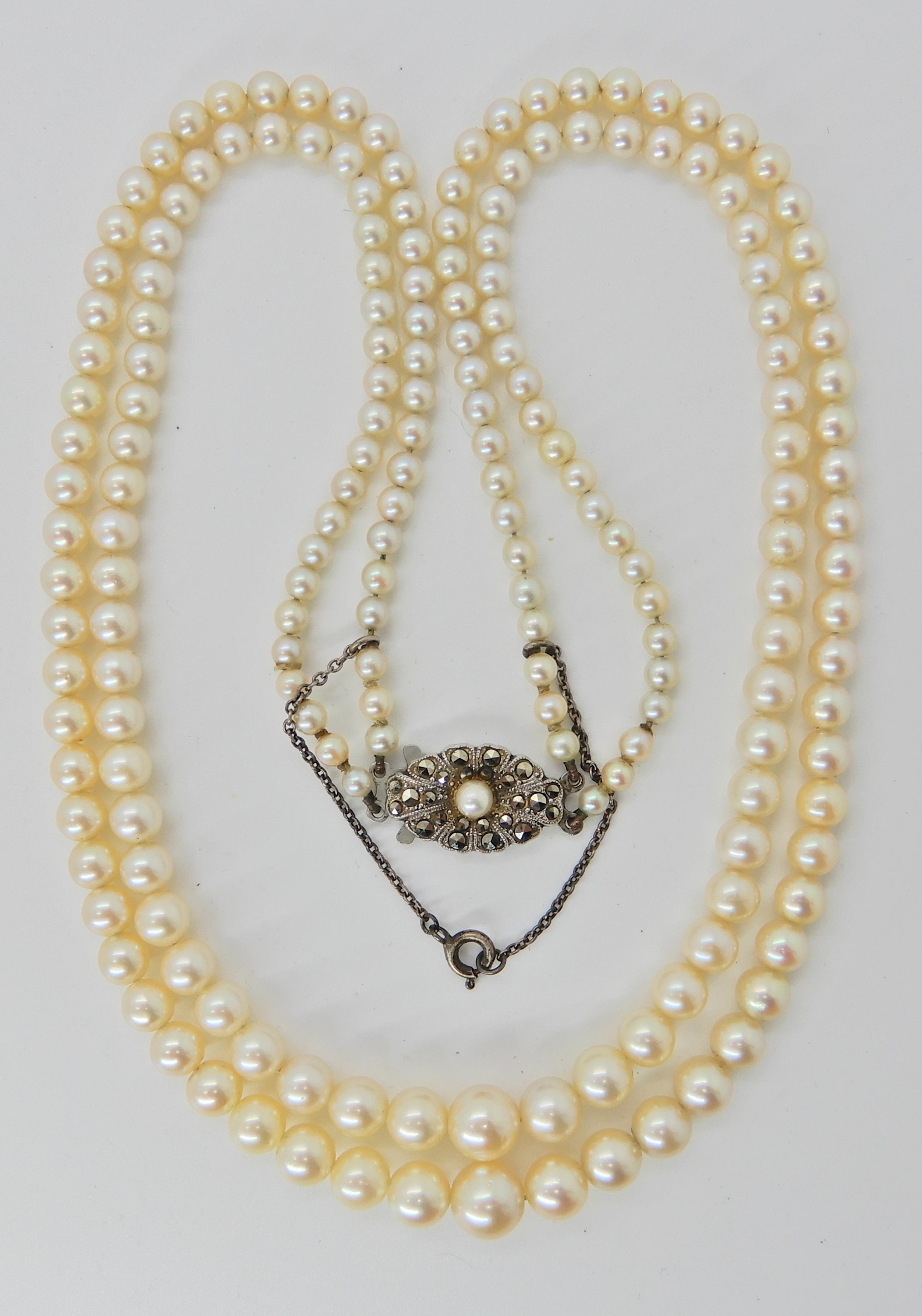 Lot 2 - A double string of cream tapered pearls with good lustre and a silver clasp, largest pearl approx
