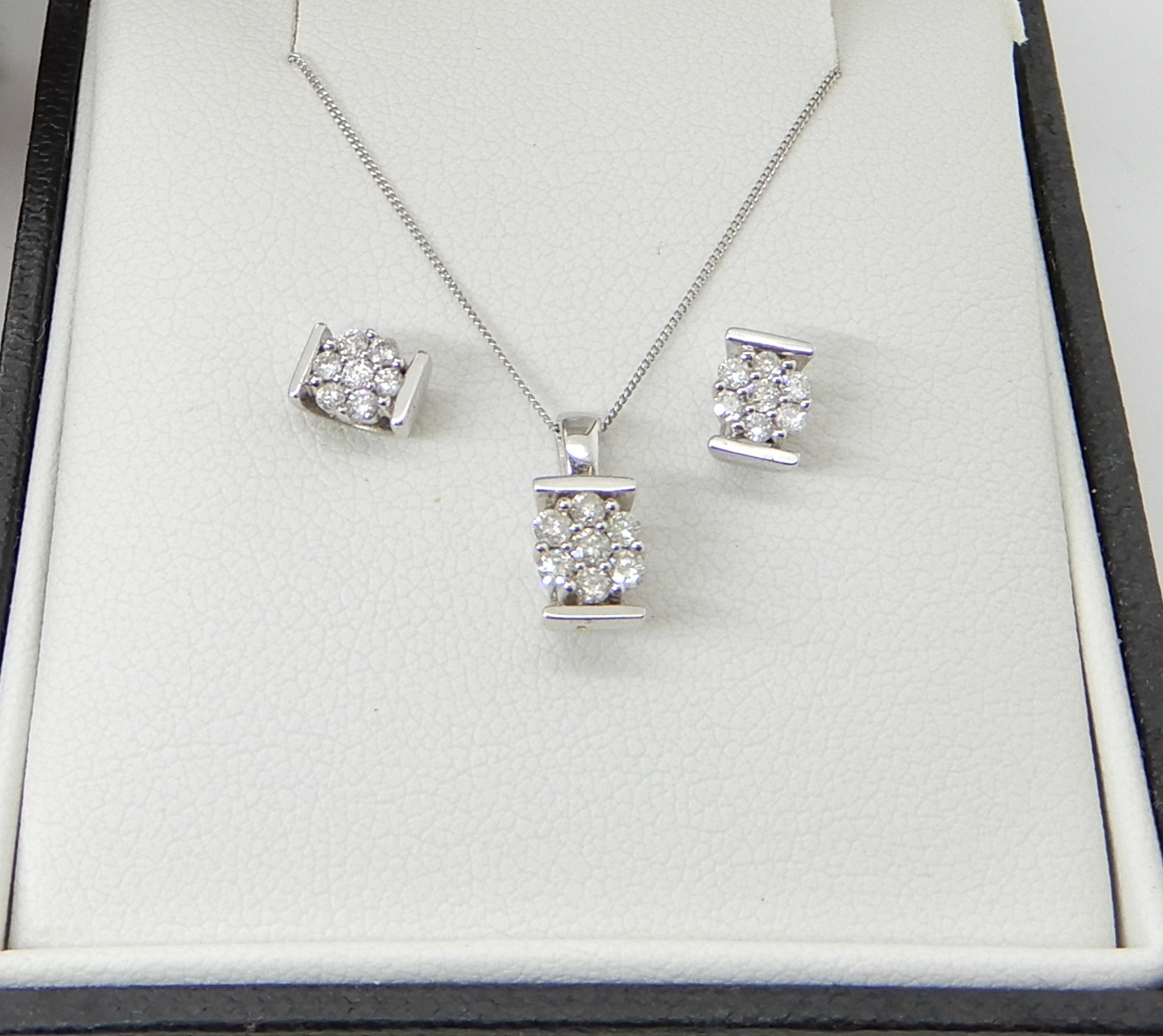 Lot 43 - A 9ct white gold flower pendant and chain and a pair of matching earrings, set with estimated approx