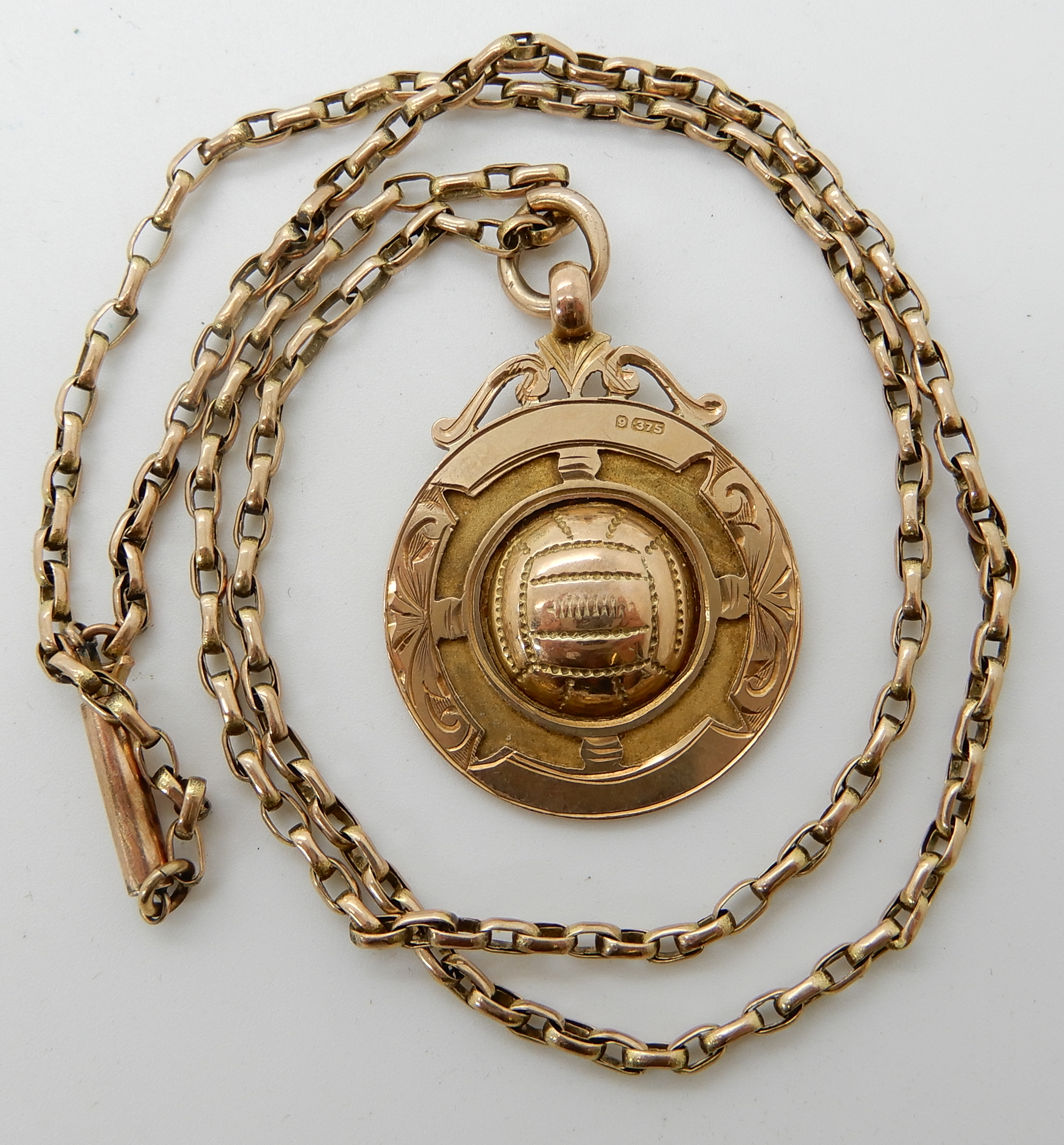 Lot 60 - A 9ct gold football medallion with a 9ct vintage chain, length of chain 48cm, weight 11gms Condition