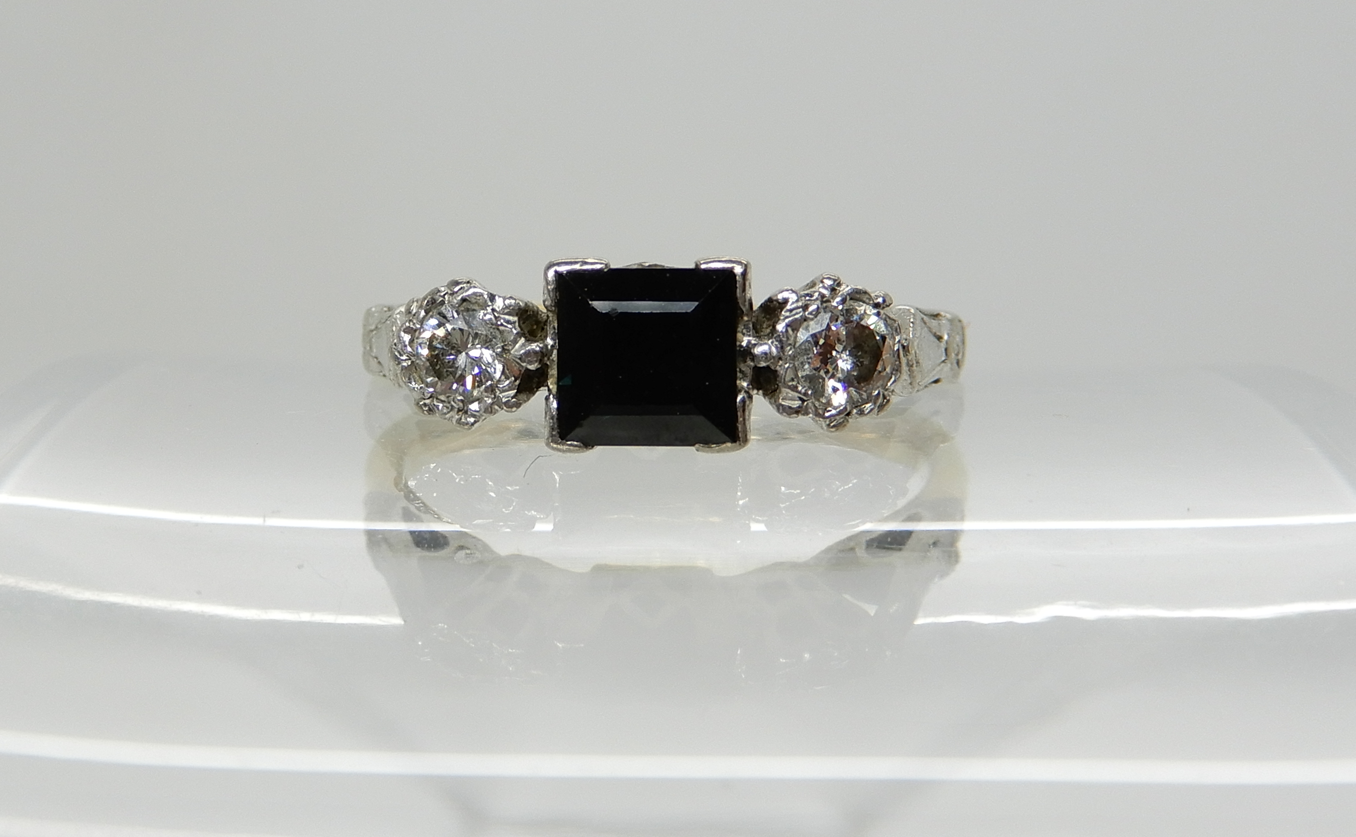 Lot 52 - An 18ct gold and platinum square cut sapphire and diamond ring, diamond content estimated approx 0.