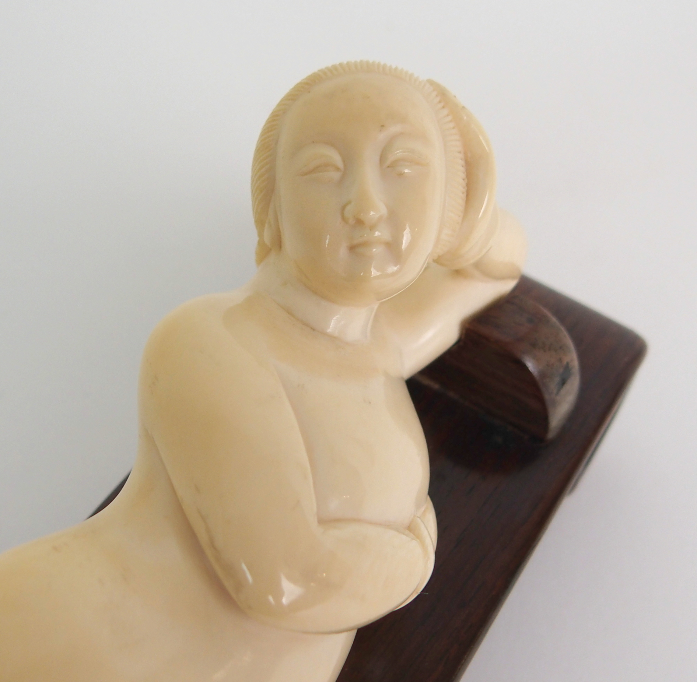 Lot 60 - A CHINESE CARVED IVORY MEDICINE LADY the reclining nude with hand on head and breast, wearing a pair