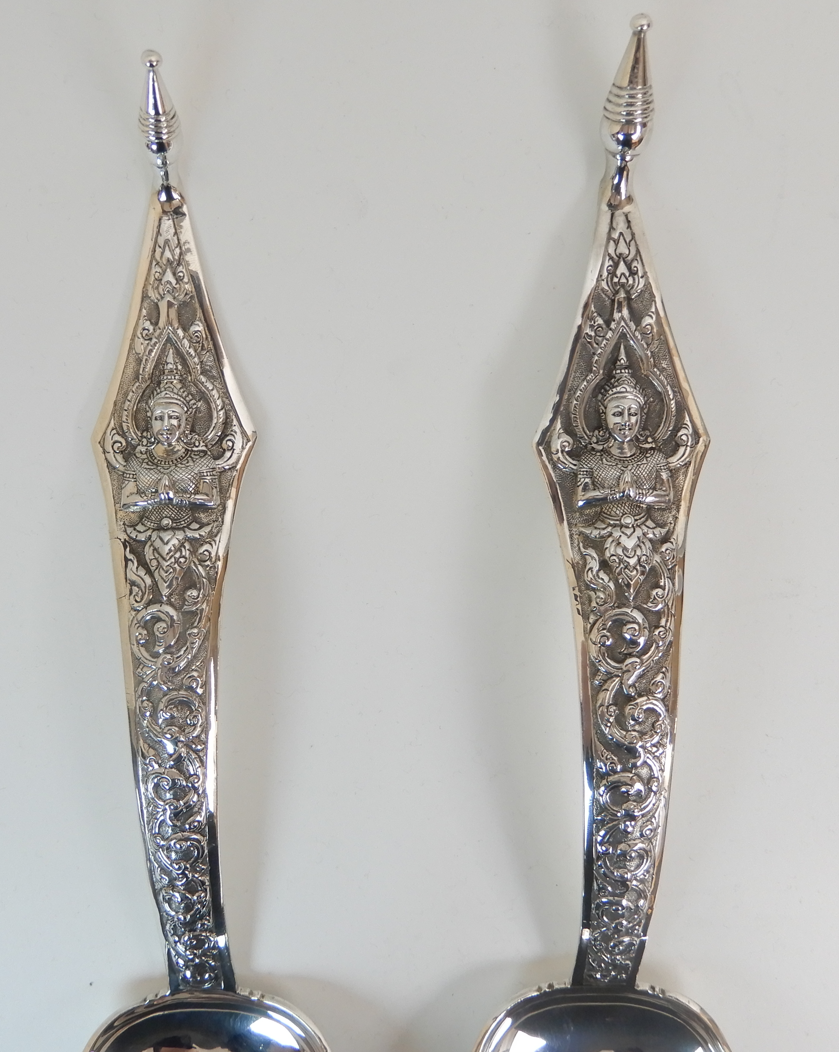 Lot 129 - A PAIR OF EASTERN SERVING SPOONS marked Thailand sterling, the shaped stem with a seated Buddha amid