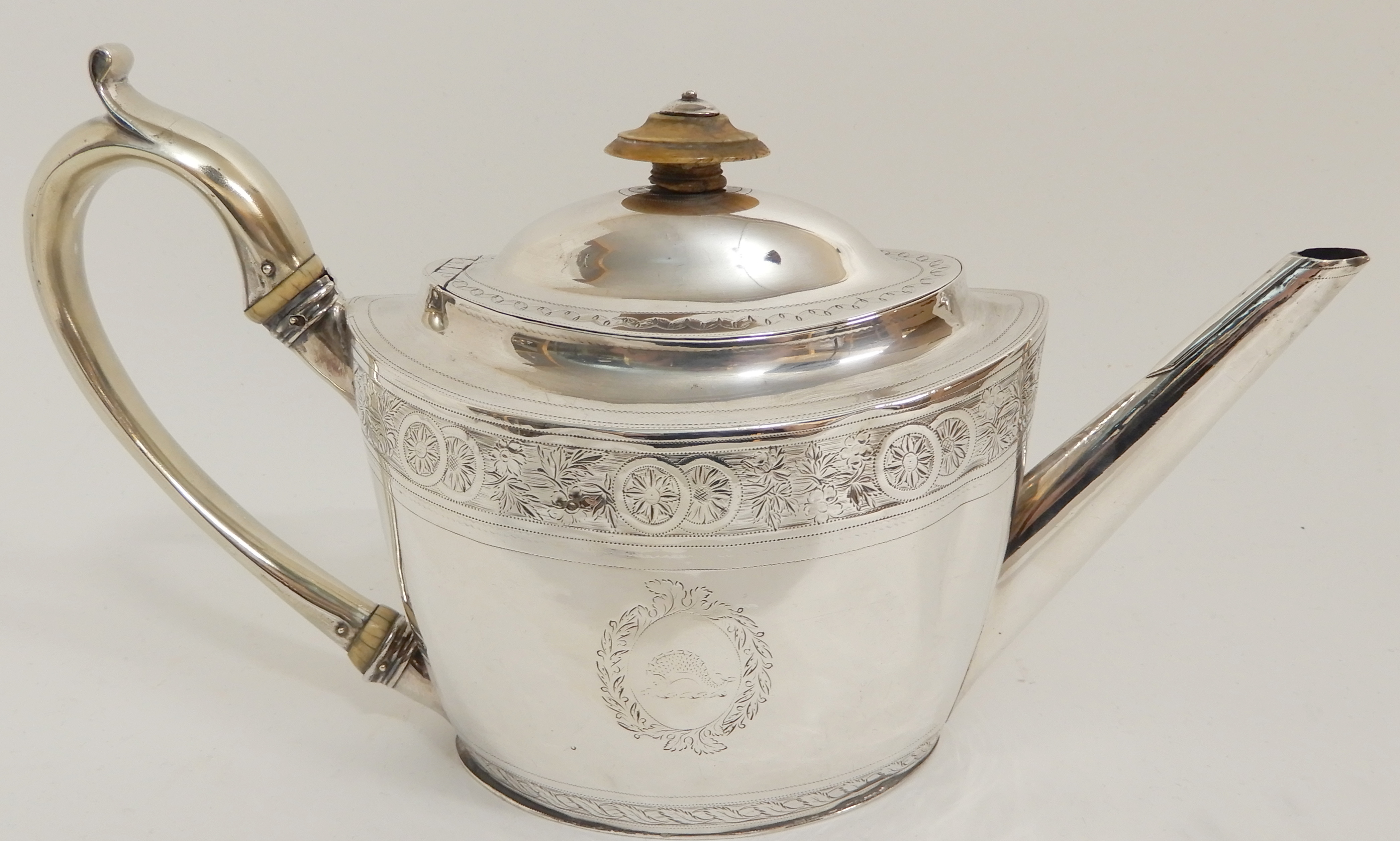 Lot 147 - A GEORGE III SILVER TEAPOT by Thomas Wallis II, London 1798, of oval form with band of roundel and