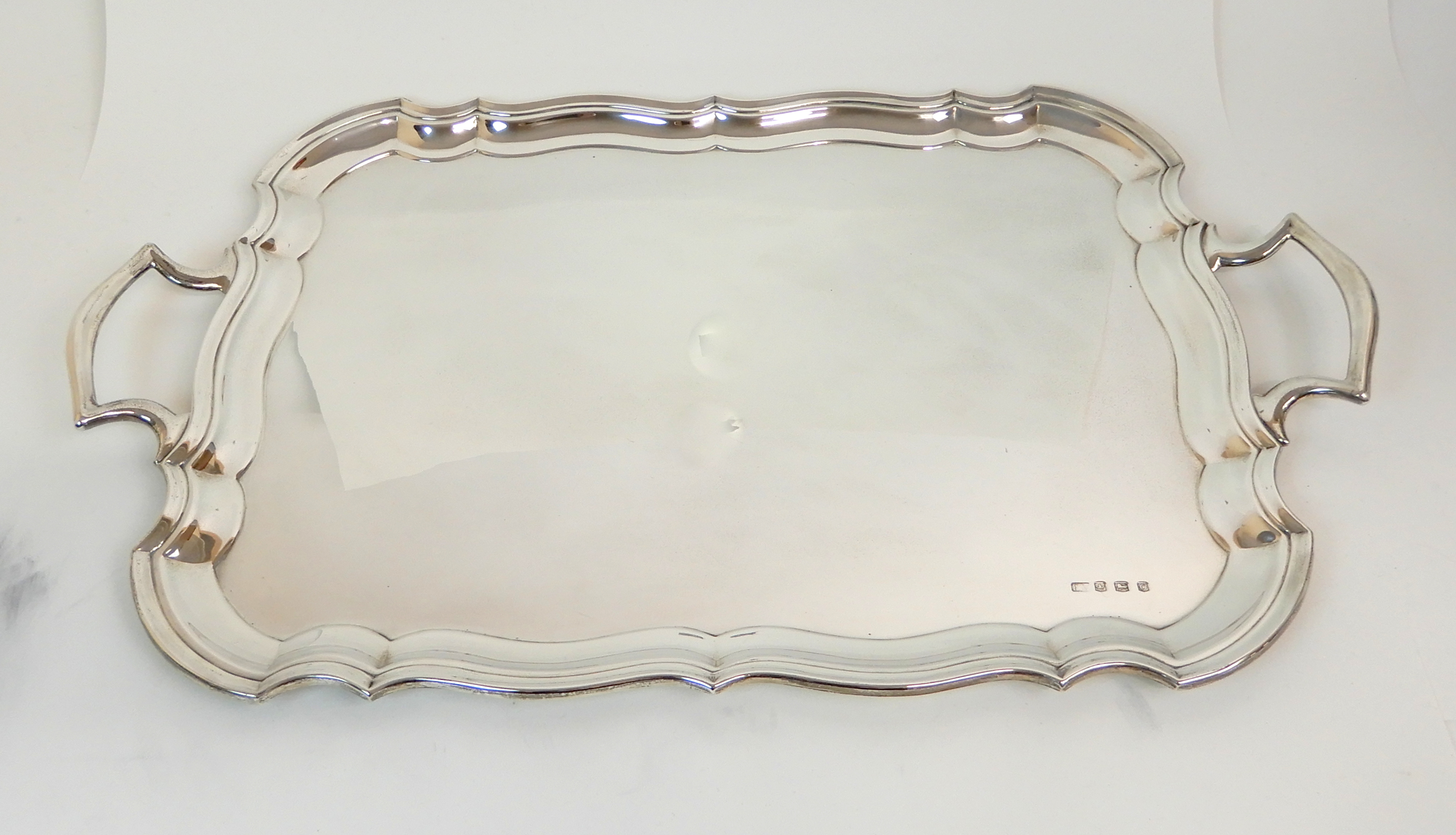 Lot 127 - A SILVER SERVING TRAY by Emile Viner, Sheffield 1931, of rectangular form with raised scalloped edge
