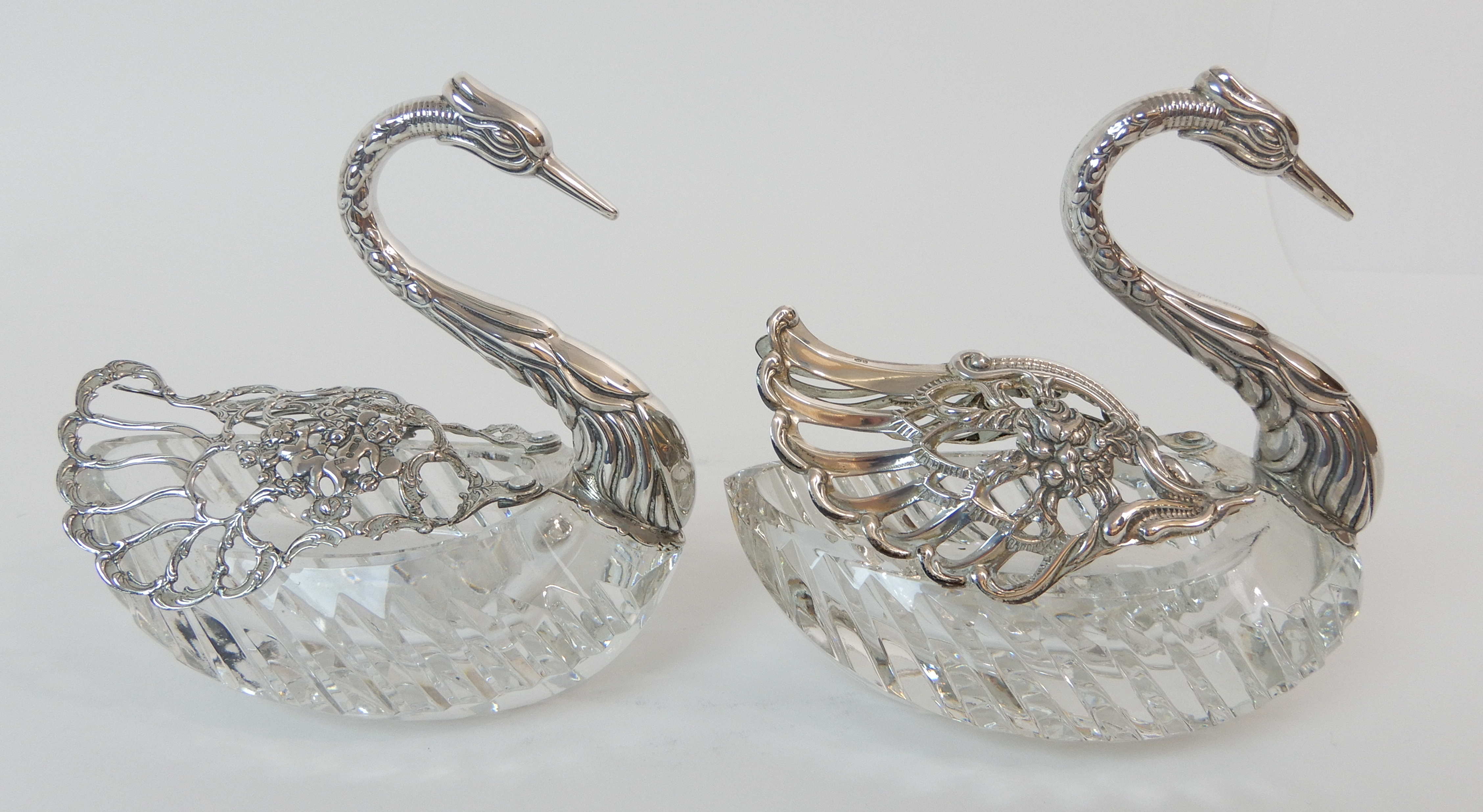 Lot 140 - FOUR CONTINENTAL SILVER AND MOULDED GLASS TRINKET DISHES marked 925, modelled as swans, the