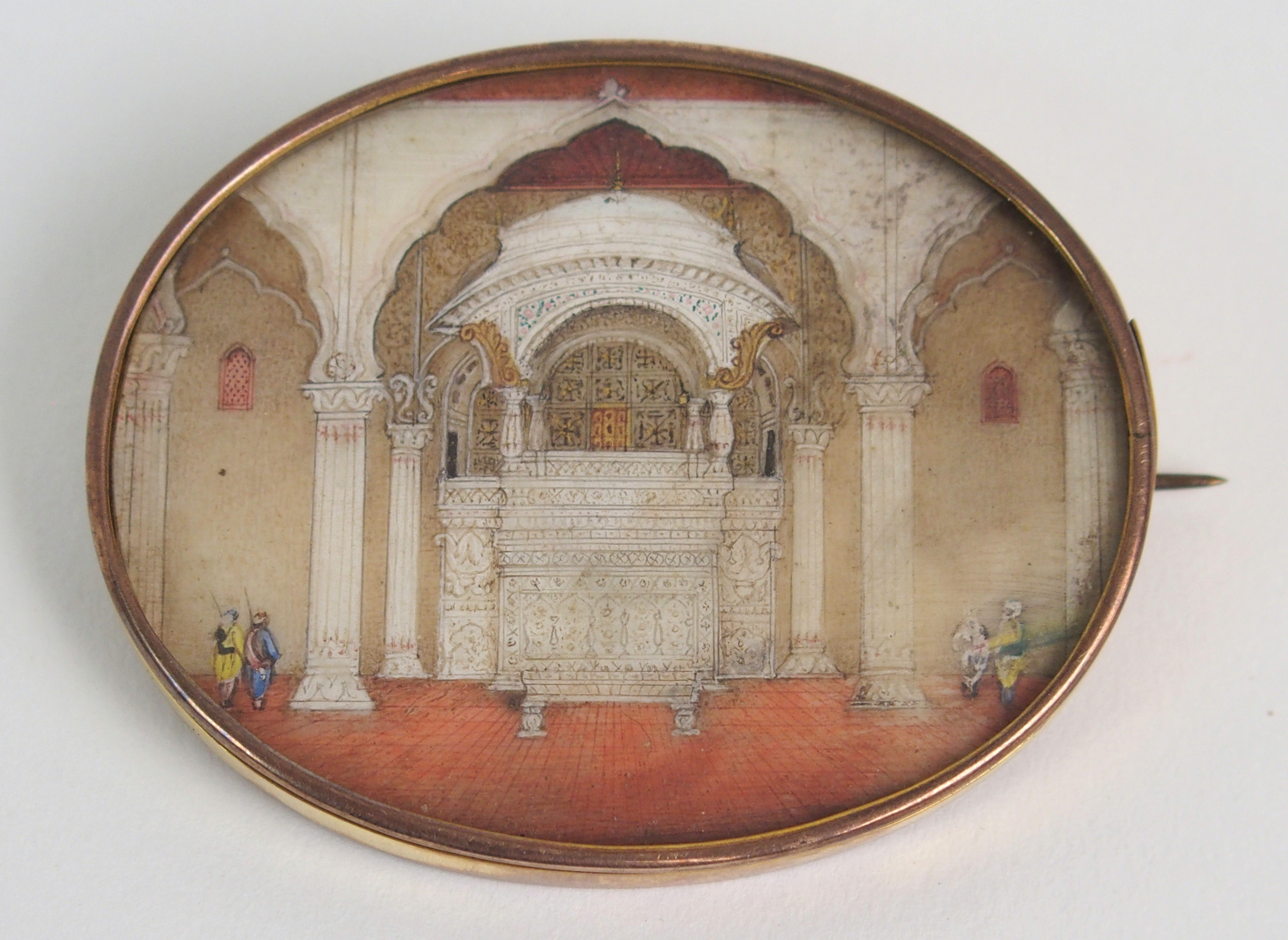 Lot 41 - AN INDIAN IVORY MINIATURE painted with military guards in a palace, gilt metal mount, 5.5cm wide and