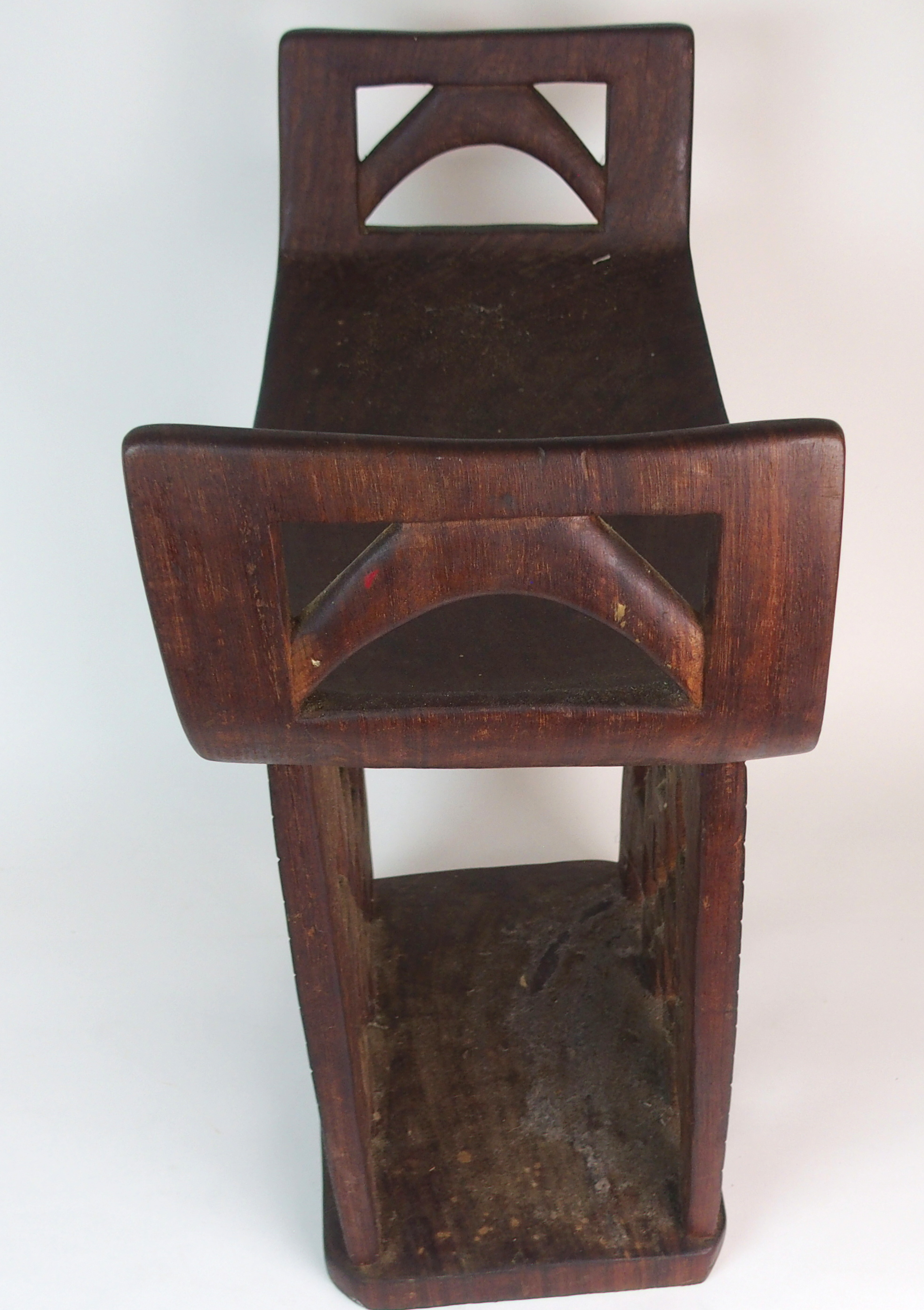 Lot 34 - *WITHDRAWN* AN AFRICAN TRIBAL HARDWOOD CIRCULAR TABLE with deep carved rim above a pair of curved