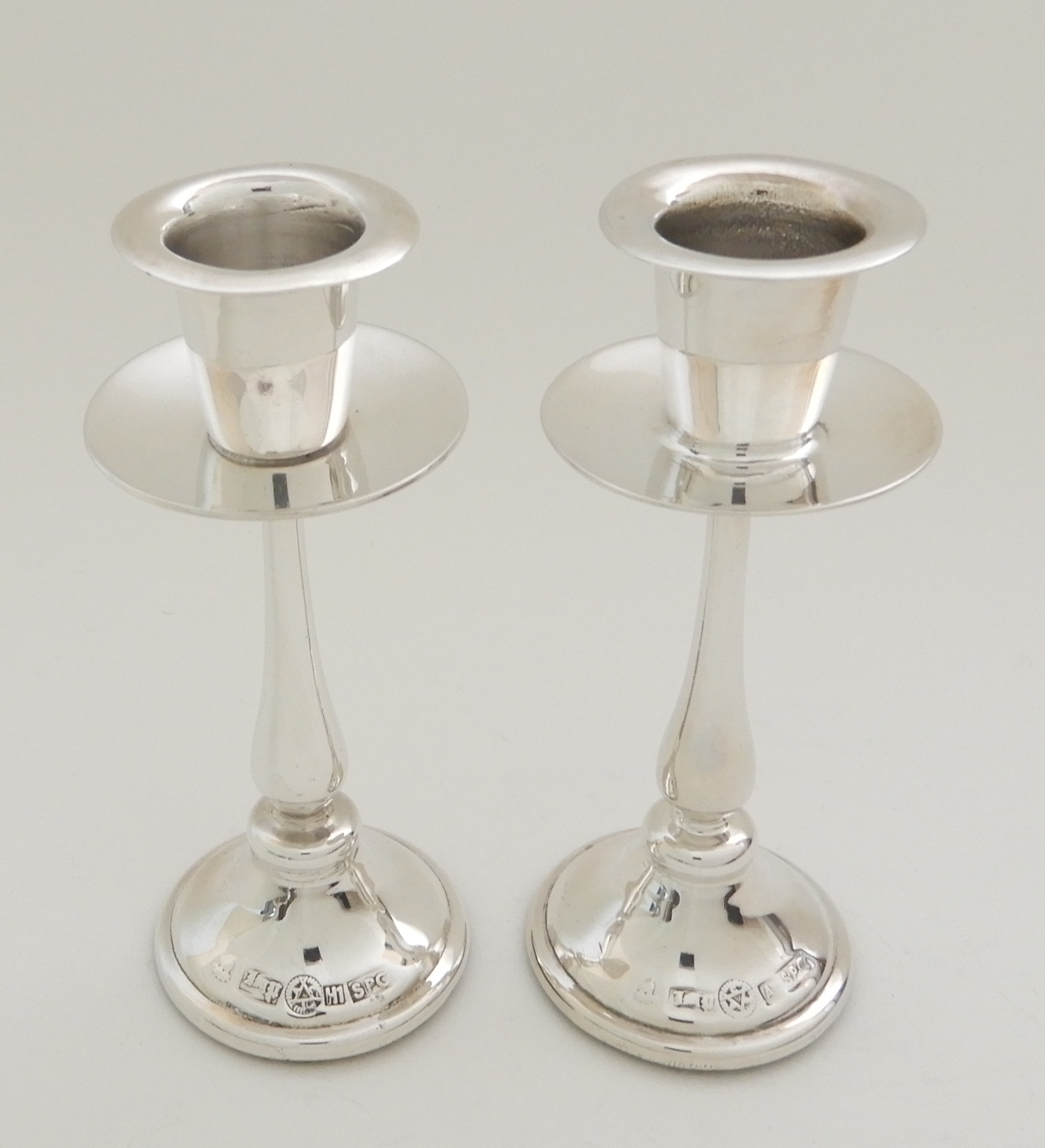 Lot 137 - A PAIR OF WHITE METAL CANDLESTICKS (POSSIBLY ISRAEL SILVER) unknown marks, with integral drip