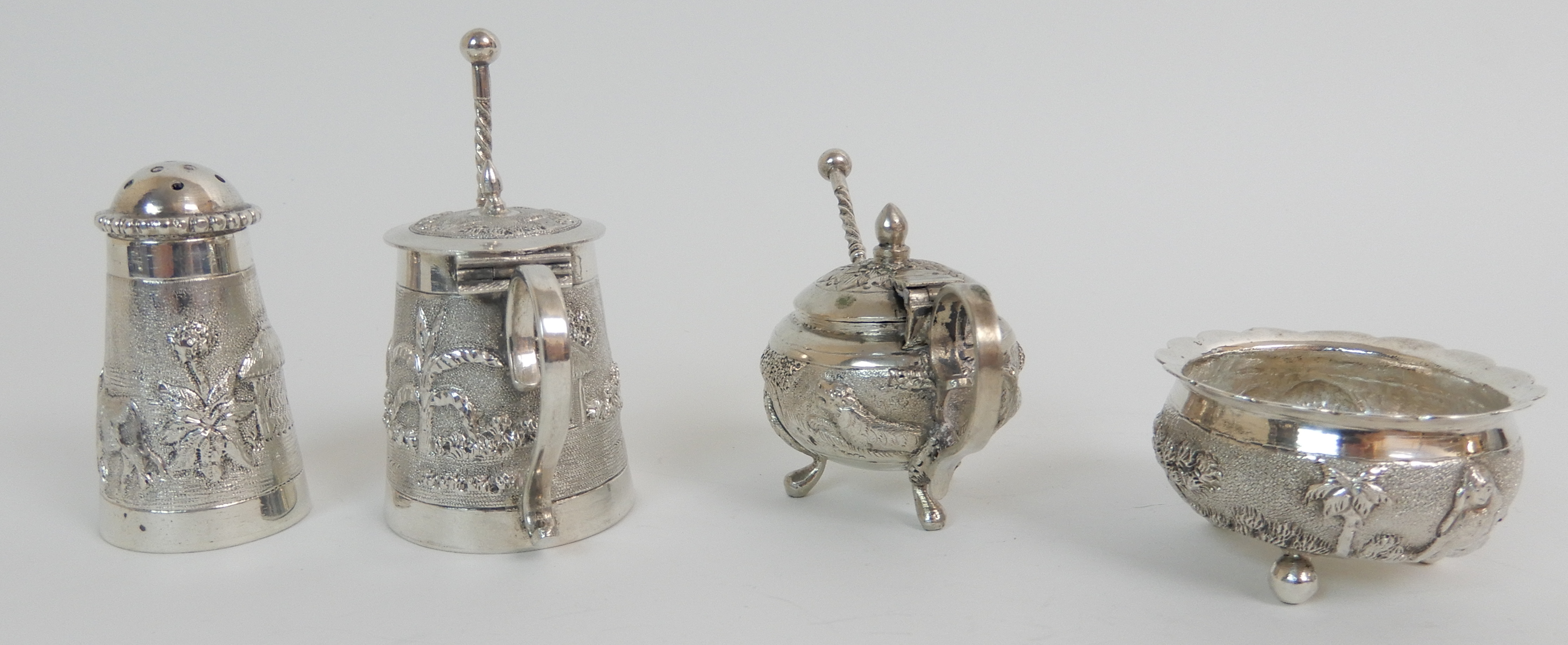 Lot 135 - FOUR BURMESE EXPORT SILVER CONDIMENTS comprising two mustard pots, a salt and a pepperette with