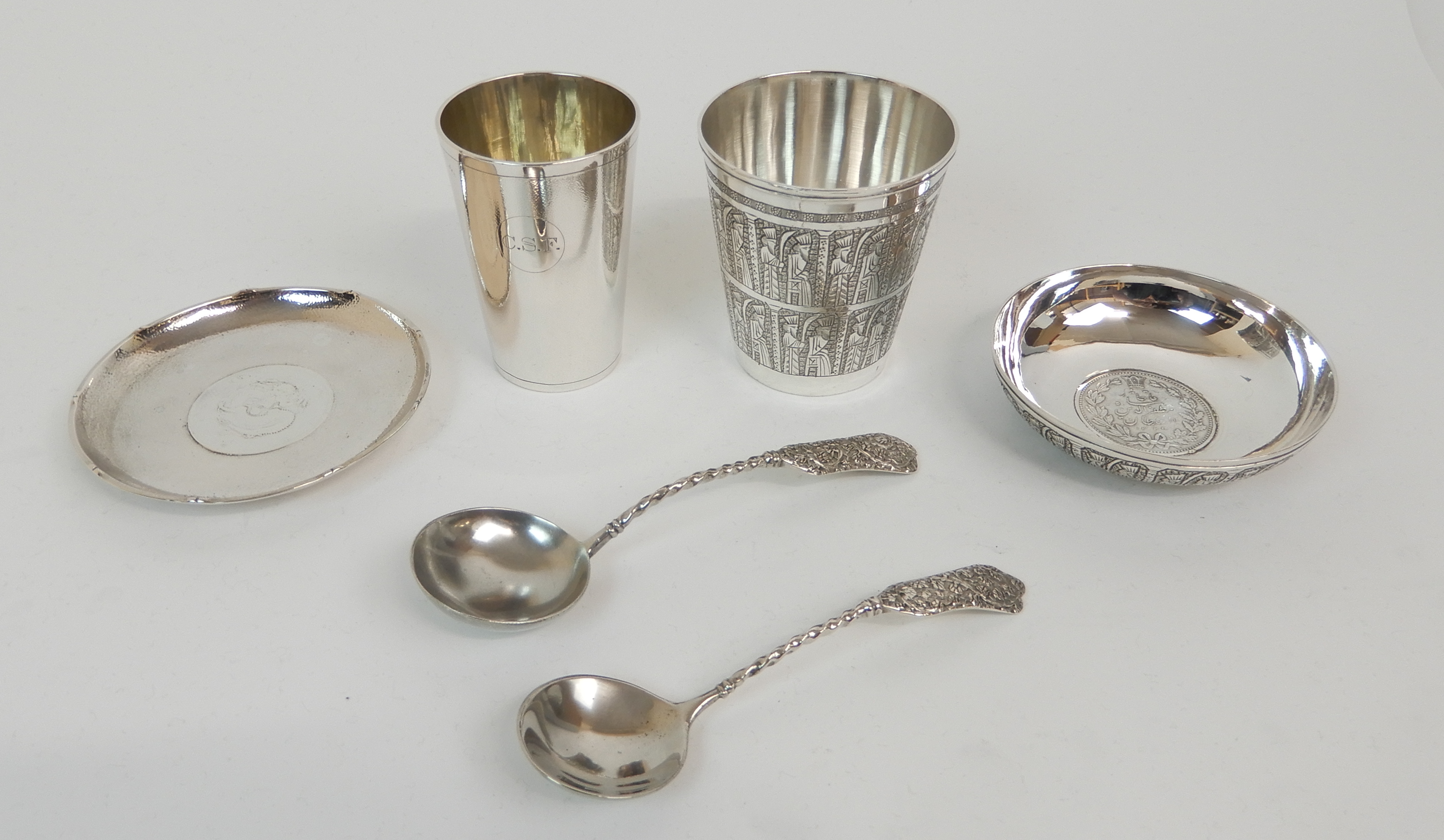 Lot 130 - A PERSIAN SILVER BEAKER marked VARTAN 84, of tapering cylindrical form, finely chased with religious