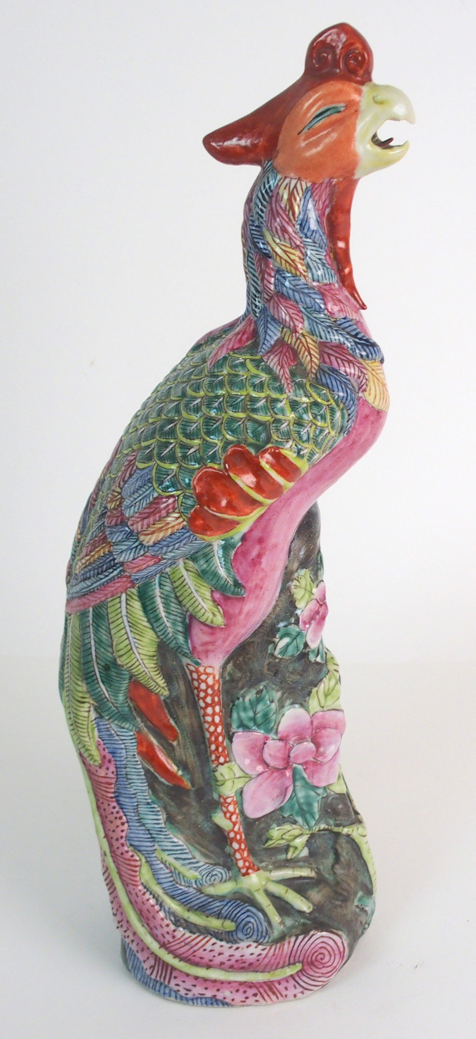 Lot 59 - A CHINESE FAMILLE ROSE MODEL OF A PEACOCK brightly coloured and standing on pierced rockwork, 36.5cm