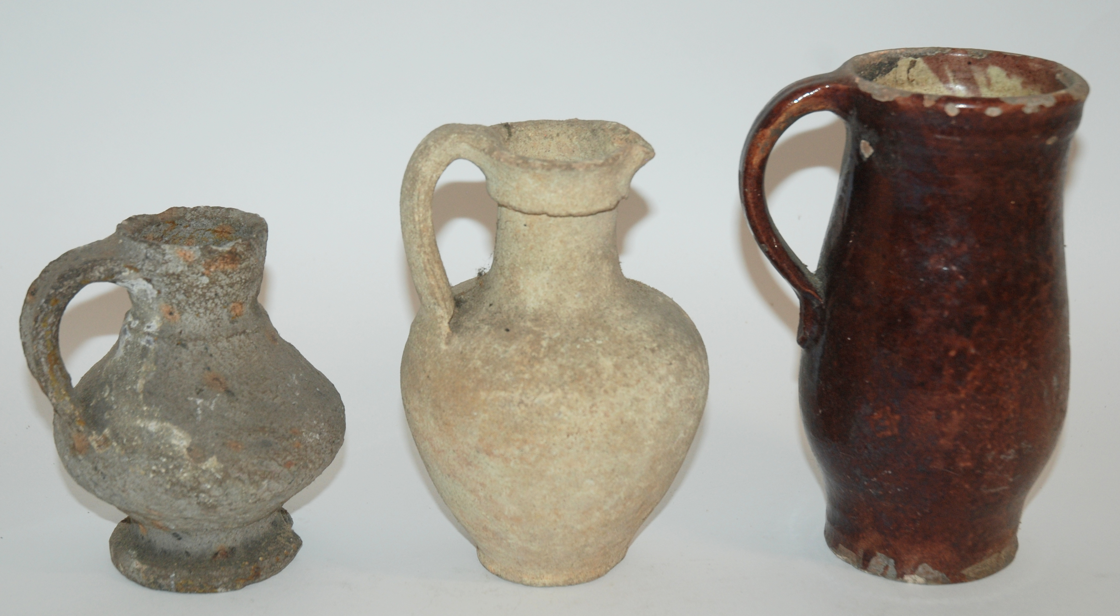 Lot 13 - A QUANTITY OF EXCAVATED PRE COLOMBIAN POTTERY SHARDS and three early pottery jugs, 13.5cm, 18cm