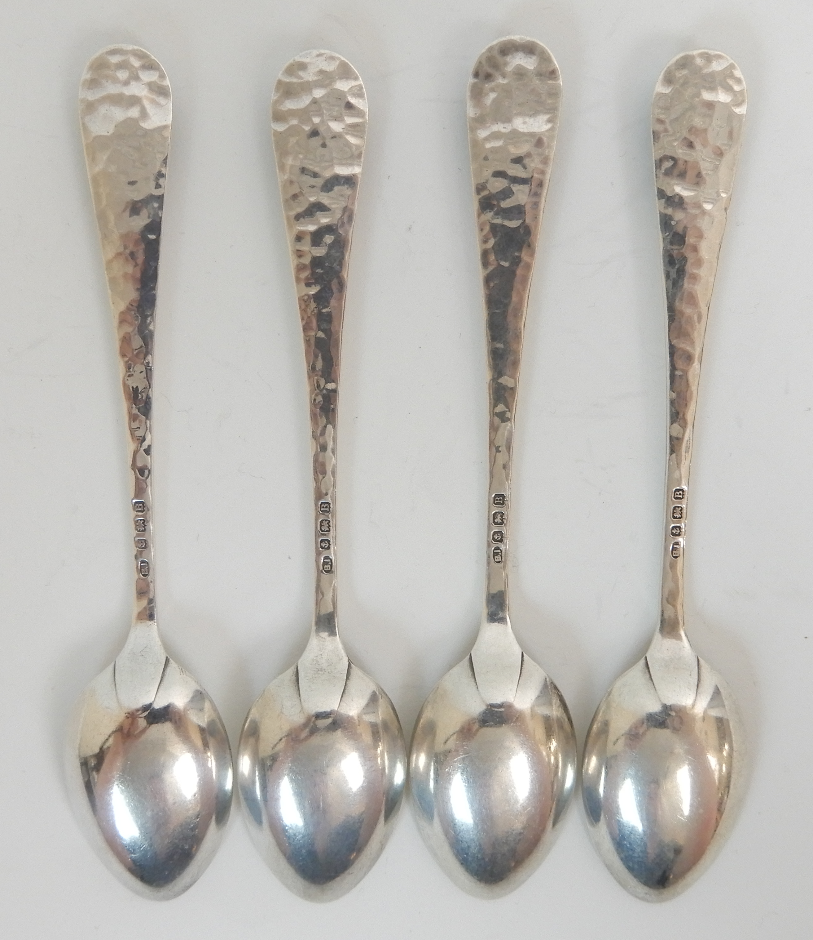 Lot 138 - A SET OF FOUR ARTS AND CRAFTS HAMMERED SILVER COFFEE SPOONS by Langstone Silver Works (Bernard