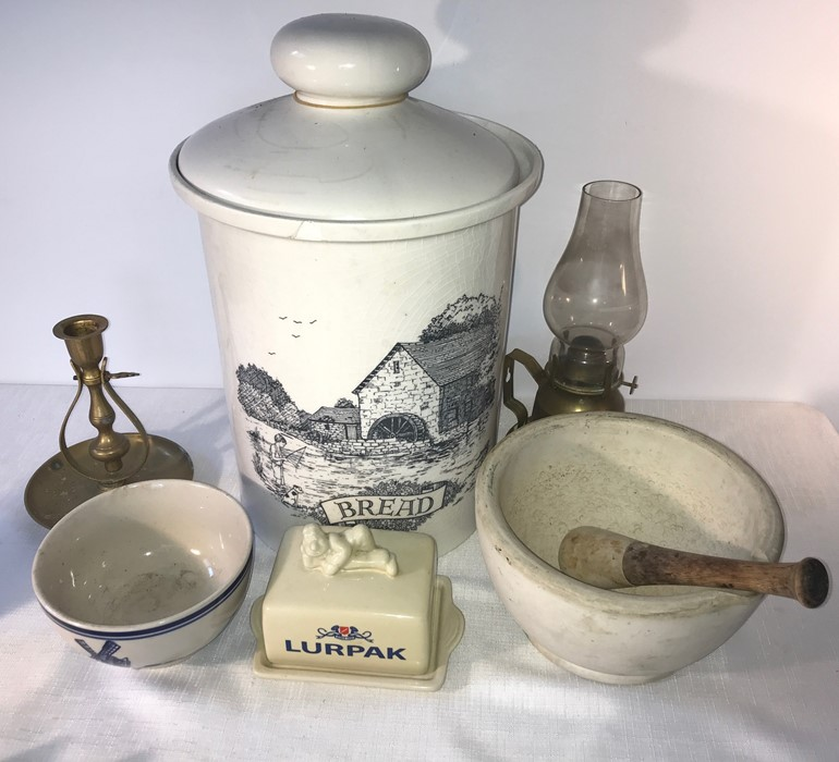Lot 53 - Lurpak butter dish, bread crock, chip to front, 2 brass lamps, a blue and white bowl and pestle