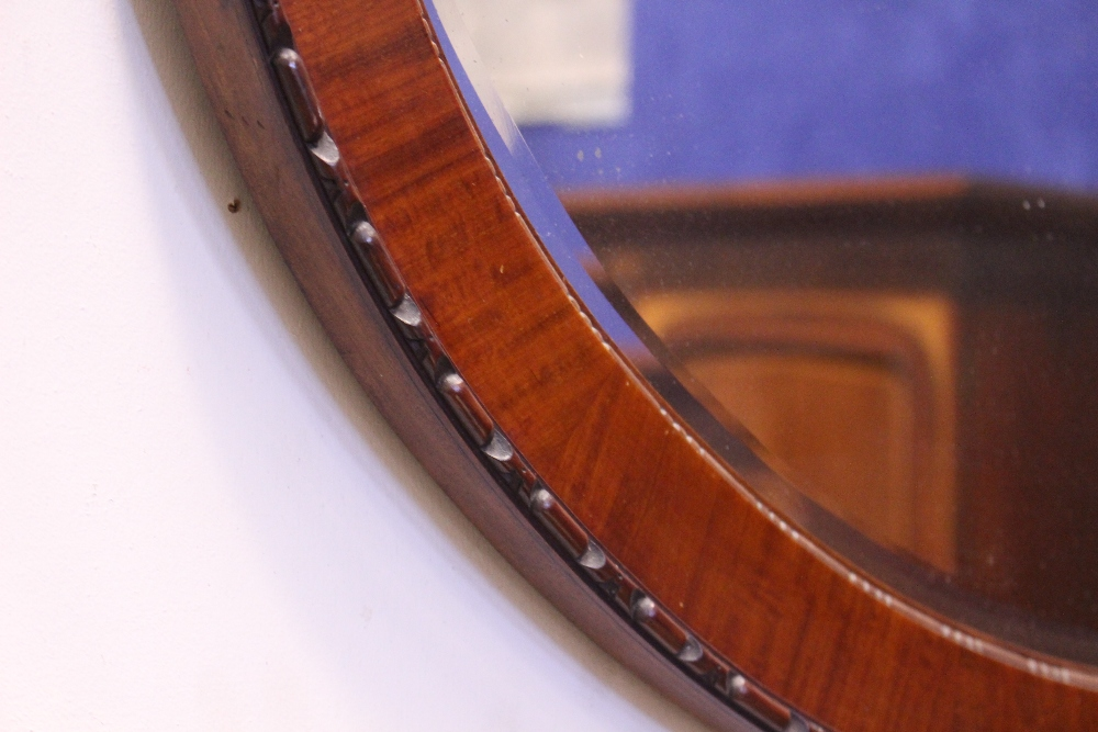 "Lot 170 - AN OVAL MAHOGANY WALL MIRROR, with gadrooned rim, 38"" x 26.5"" approx"
