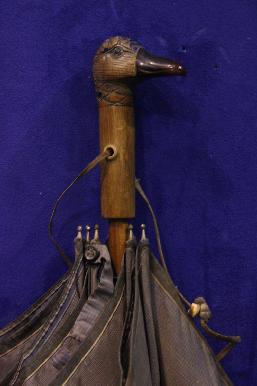 "Lot 136 - A LADY'S PARASOL / UMBRELLA, with carved duck head handle, by the maker H. Johnson Ltd, 25"" long,"