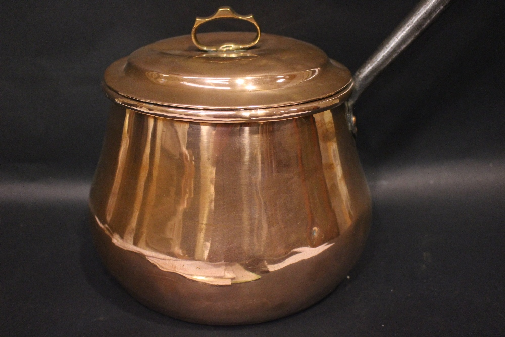 """Lot 322 - A COPPERWARE POT, with lid, and cast iron handle, 8"""" tall, 10"""" length of handle, provenance came"""