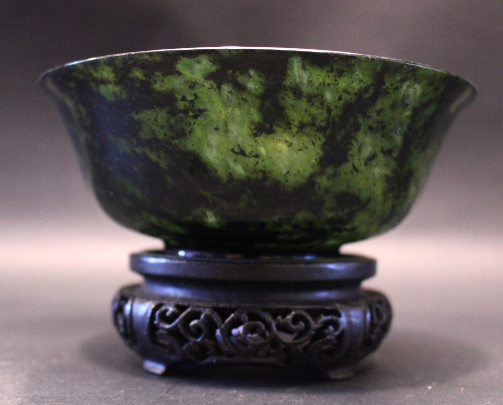 """Lot 35 - A SPINACH JADE BOWL, sitting on a carved wooden stand, 5"""" diameter approx"""