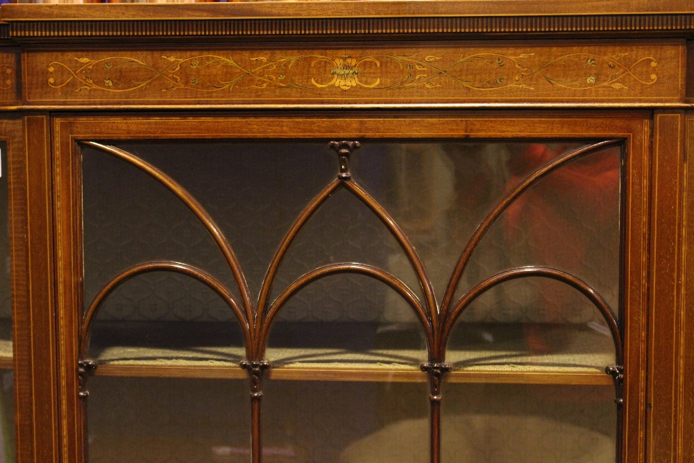 Lot 21 - A FINE BOW ENDED BREAKFRONT GLAZED DISPLAY CABINET, decorated with marquetry & string inlaid