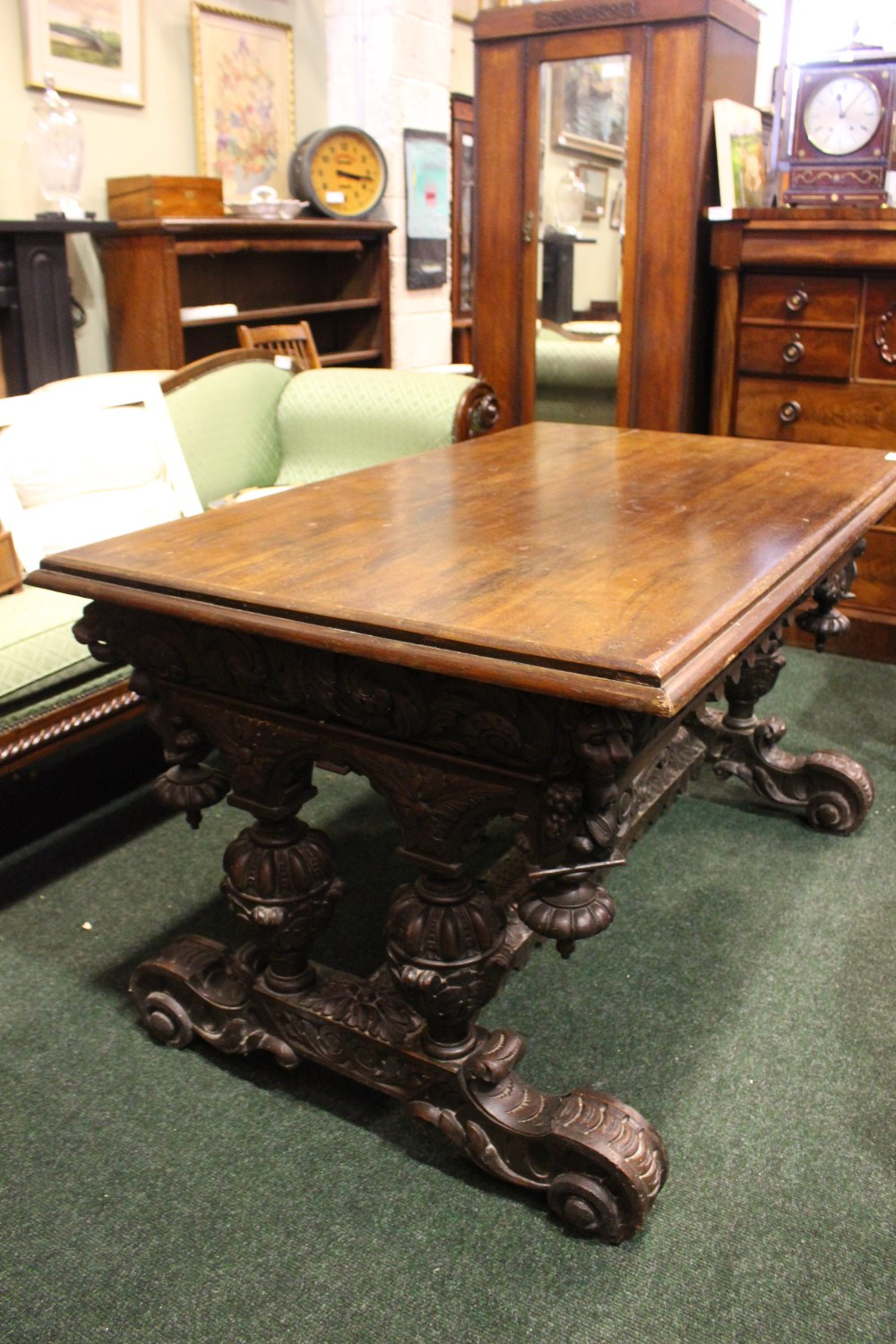Lot 54 - A VERY LARGE OAK CARVED 19TH CENTURY TRESTLE TABLE, with carved lion head canted corners, raised