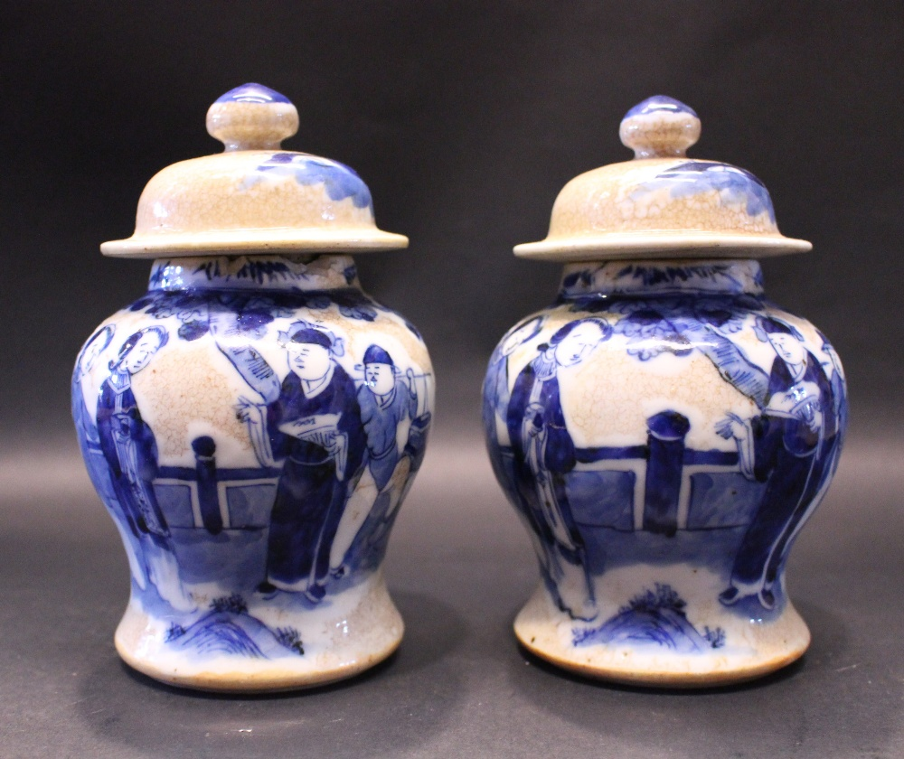Lot 36 - A PAIR OF BLUE & WHITE MINIATURE GINGER JARS, crackle glazed, each with images of figures in