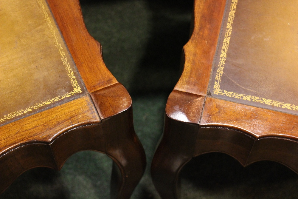"""Lot 51 - A PAIR OF SERPENTINE SHAPED LEATHER TOPPED TABLES, raised on cabriole shaped legs 26"""" x 19"""" x 22"""""""