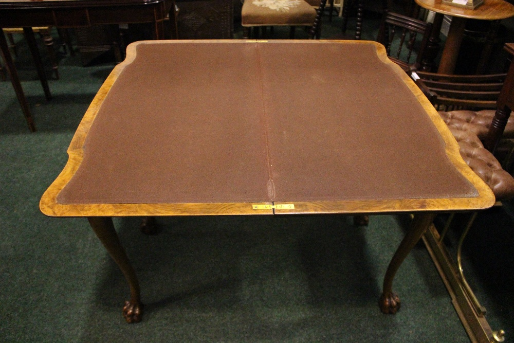 Lot 9 - A VERY FINE WALNUT FOLD OVER CARD TABLE, with gadrooned rim of foliage detail, raised on cabriole