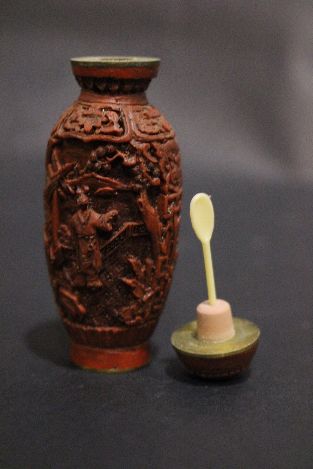 Lot 56 - A CARVED CINNABAR & BRASS SNUFF BOTTLE, with inlaid brass character marks to the base, decorated
