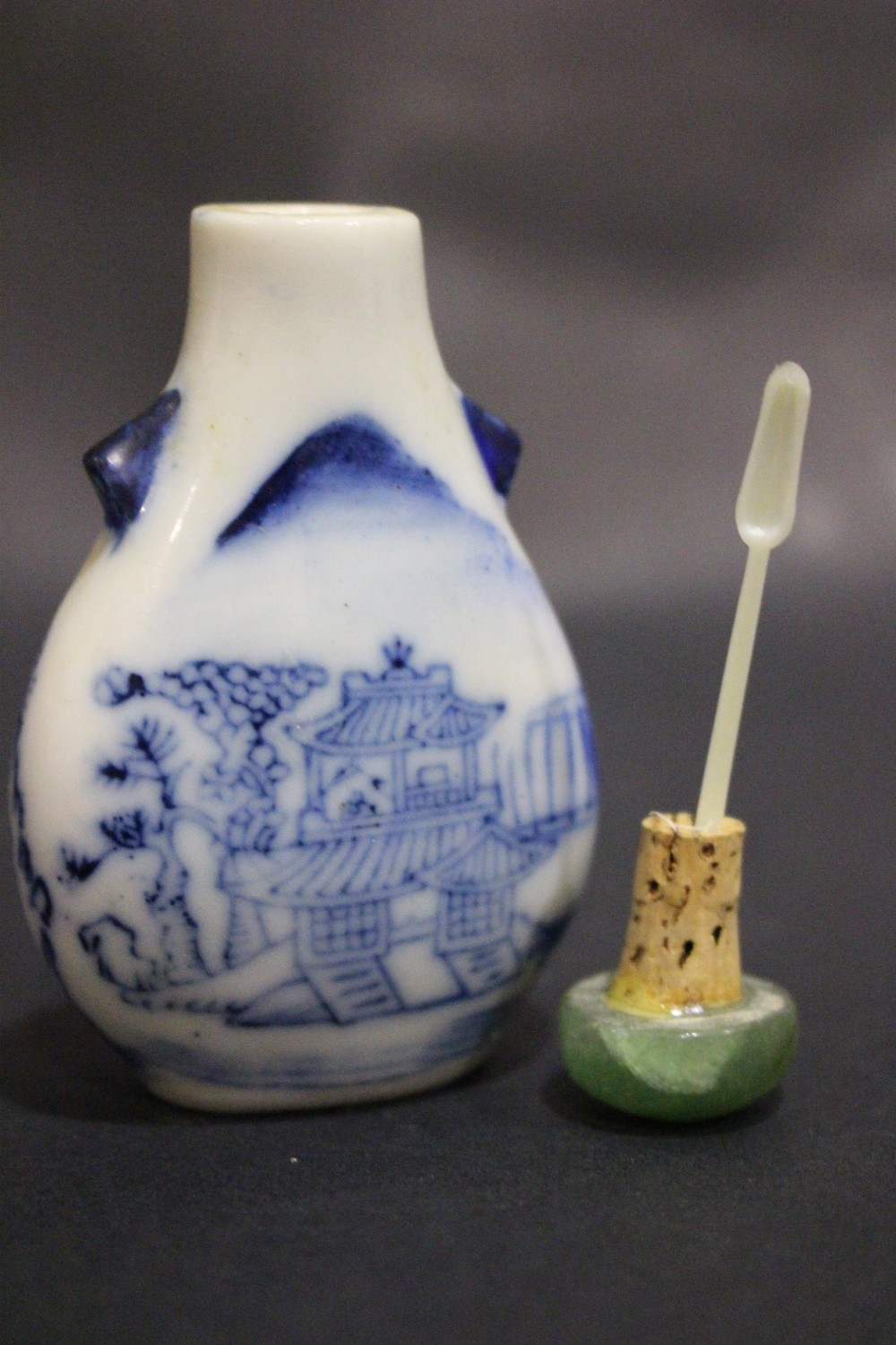 Lot 55 - A BLUE & WHITE CHINESE SNUFF BOTTLE, with a jade stopper and spoon, decorated with landscape and