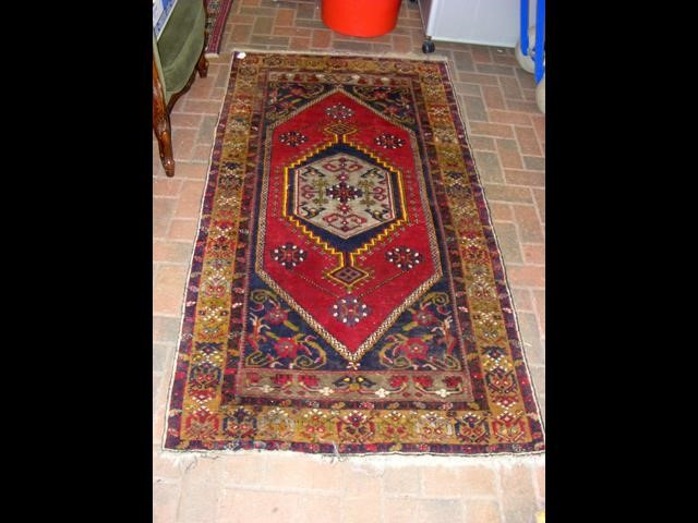 Lot 29 - A Middle Eastern red ground rug with triple border