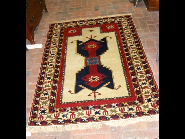 Lot 34 - A Middle Eastern rug with fawn and red ground - 17