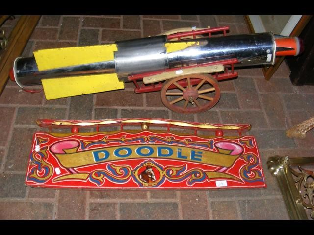 Lot 34 - An old painted fairground sign 'Doodle', together with a fairground metal rocket and wagon
