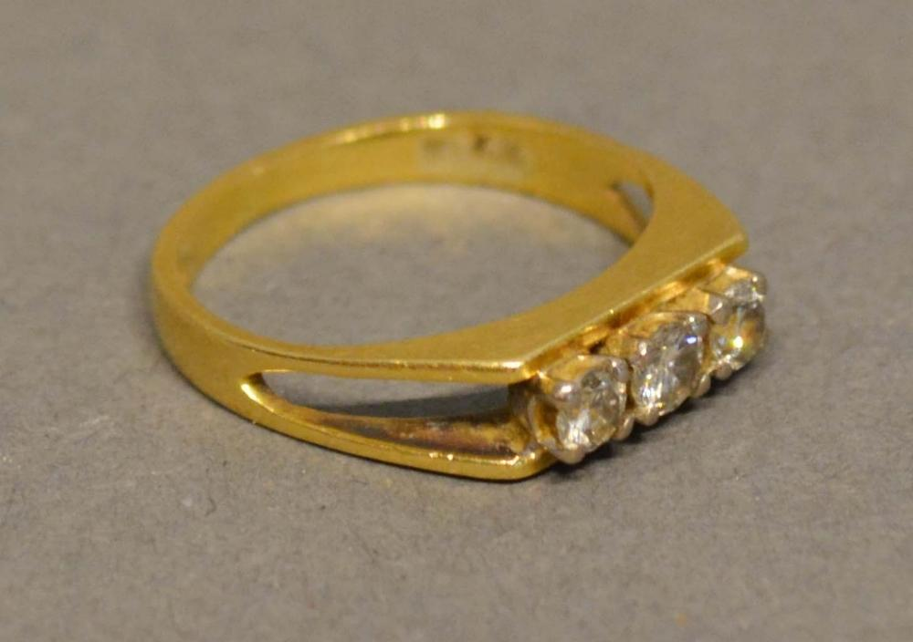 Lot 199 - An 18 Carat Yellow Gold Three Stone Diamond Ring set with three diamonds within an unusual pierced