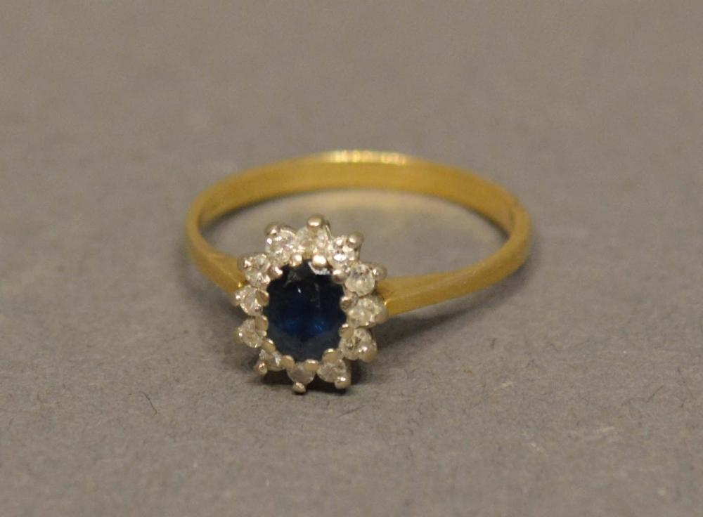 Lot 201 - An 18 Carat Yellow Gold Sapphire and Diamond Cluster Ring set with oval sapphire surrounded by