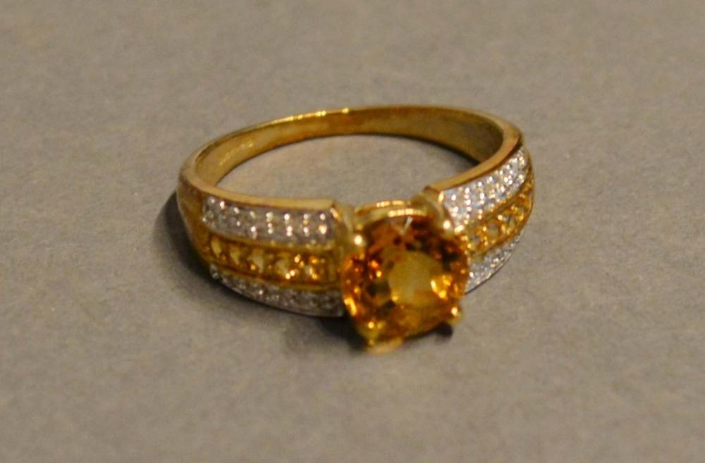 Lot 162 - A 9 Carat Gold Citrine Diamond Set Ring with a large citrine flanked by bands of diamonds