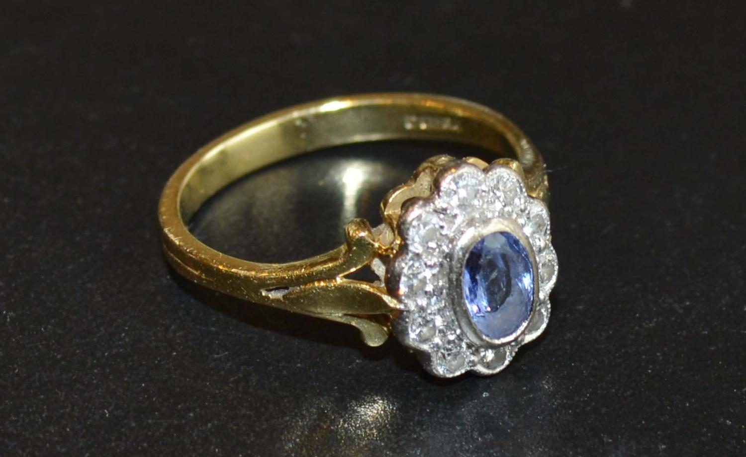 Lot 219 - An 18 Carat Gold Tanzanite and Diamond Ring set with an oval tanzanite surrounded by diamonds