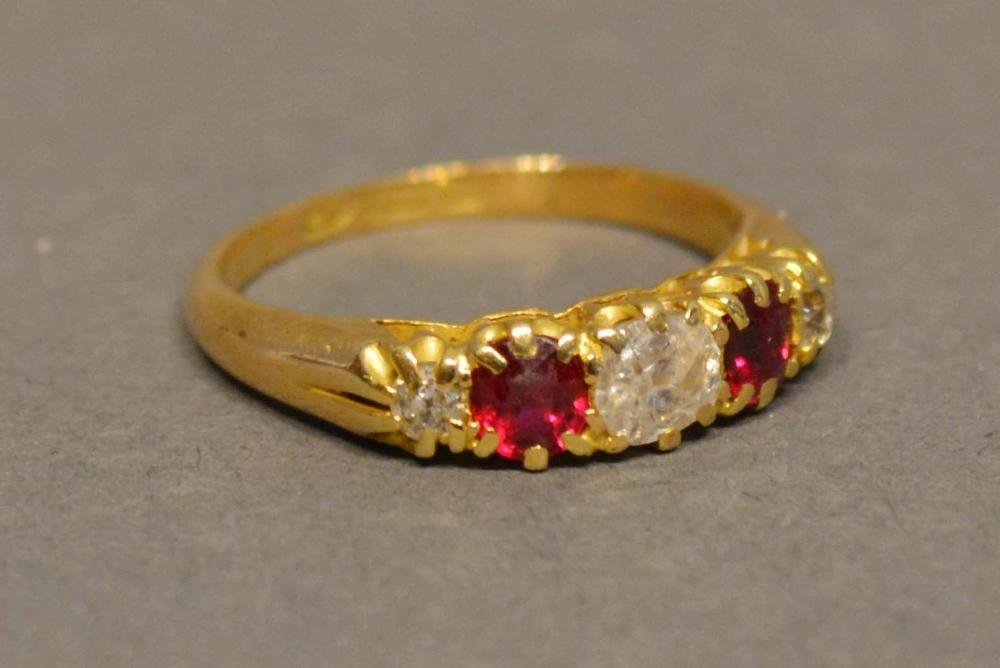 Lot 200 - An 18 Carat Yellow Gold Diamond and Ruby Ring set with three diamonds and two rubies in a pierced