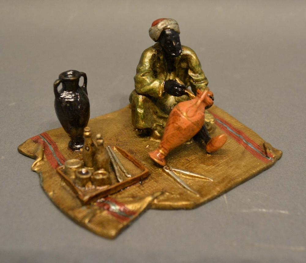 Lot 285 - An Austrian Cold Painted Bronze Model in the form of an Arab on a rug with various implements, 10